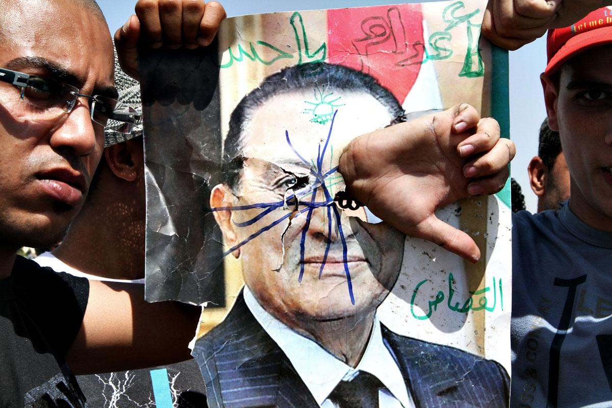 "On June 2, 2012, protesters defaced a poster of ex-president Hosni Mubarak moments before the announcement that he got life in prison for the ""complicity in the deaths of hundreds of protesters."""