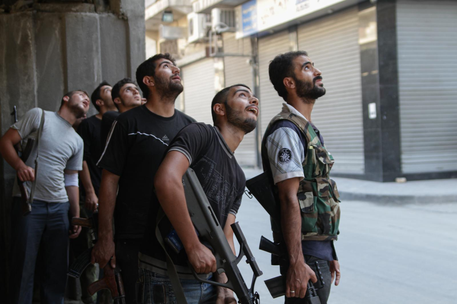 The Free Syrian Army hide underneath a highway in a neighborhood in Aleppo on August 21, 2012 as Assad's forces fly above trying to target certain areas that are FSA strongholds.