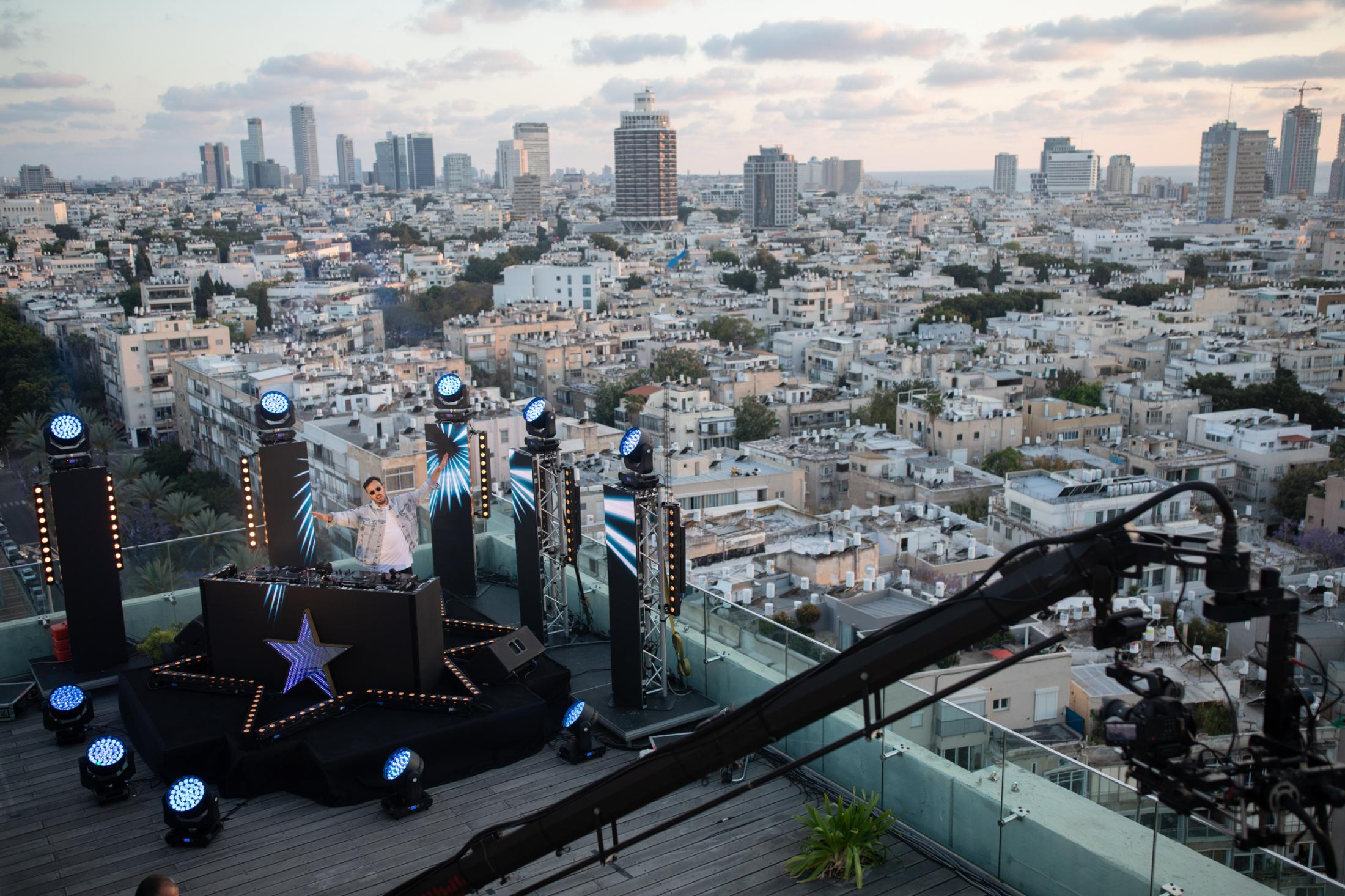 """DJ Itay Galo, 33, performs during an online party that is broadcasted live via Zoom and Facebook Live, from the roof of the Tel Aviv municipality building, Tel Aviv, Israel, April 29, 2020. """"It's like a fake, it's not the real thing, but everybody tags me on Facebook and Instagram, they watch me and I like it. It's good for this situation, but after the Corona I want to see the crowd."""""""