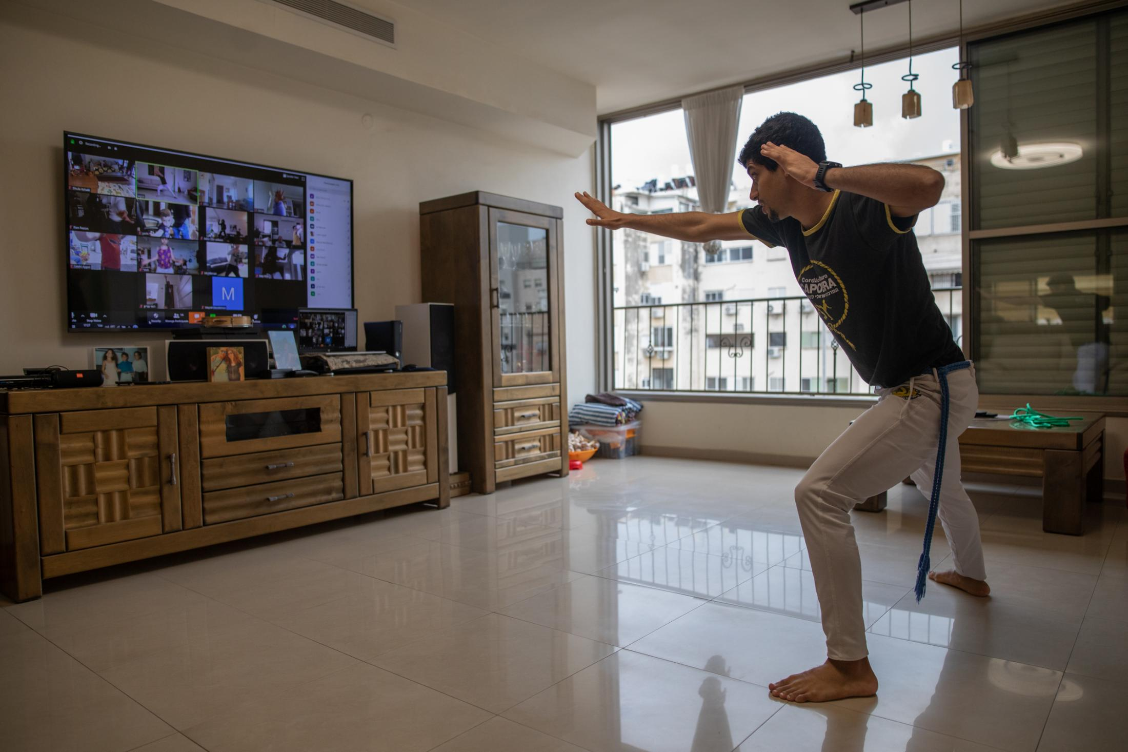 """Capoeira instructor Gal Maabari, 25, gives an online Capoeira lesson for children on Zoom in his home in Tel Aviv, Israel, April 16, 2020. """"For me it's a positive experience. Giving an online course makes me think about the 'Why', about the purpose of why I'm doing it. It's like resetting the whole concept of work, of everything. It makes me creative because now I need to think about the interaction with the students. Everything I do in the physical class, like giving feedback or demonstrating something, I do automatically; everything I do in the online classes, I understand better now."""""""