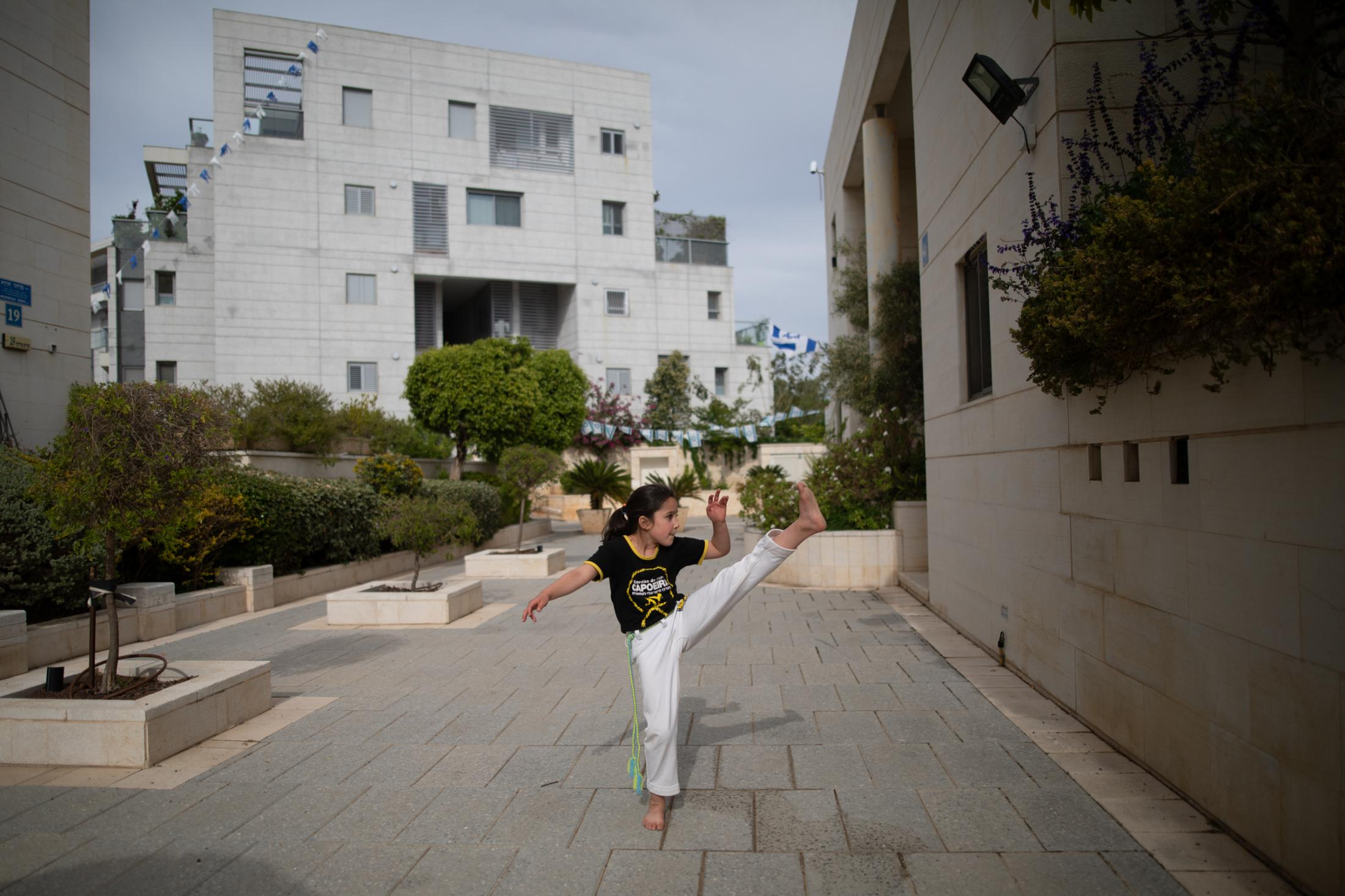 """Gaya Jacobs, 7, takes an online Capoeira class via Zoom on her phone, which she adjusted to the wall in front of her home in Tel Aviv, Israel, April 27, 2020. """"It feels weird to me because I am together with all my friends all the time and I see the teacher and I train in the studio, and one day they are telling me 'You cannot train here anymore, from now on you are training at home'. That wasn't nice, that wasn't fun, but I am dealing with it. It's not so bad."""""""