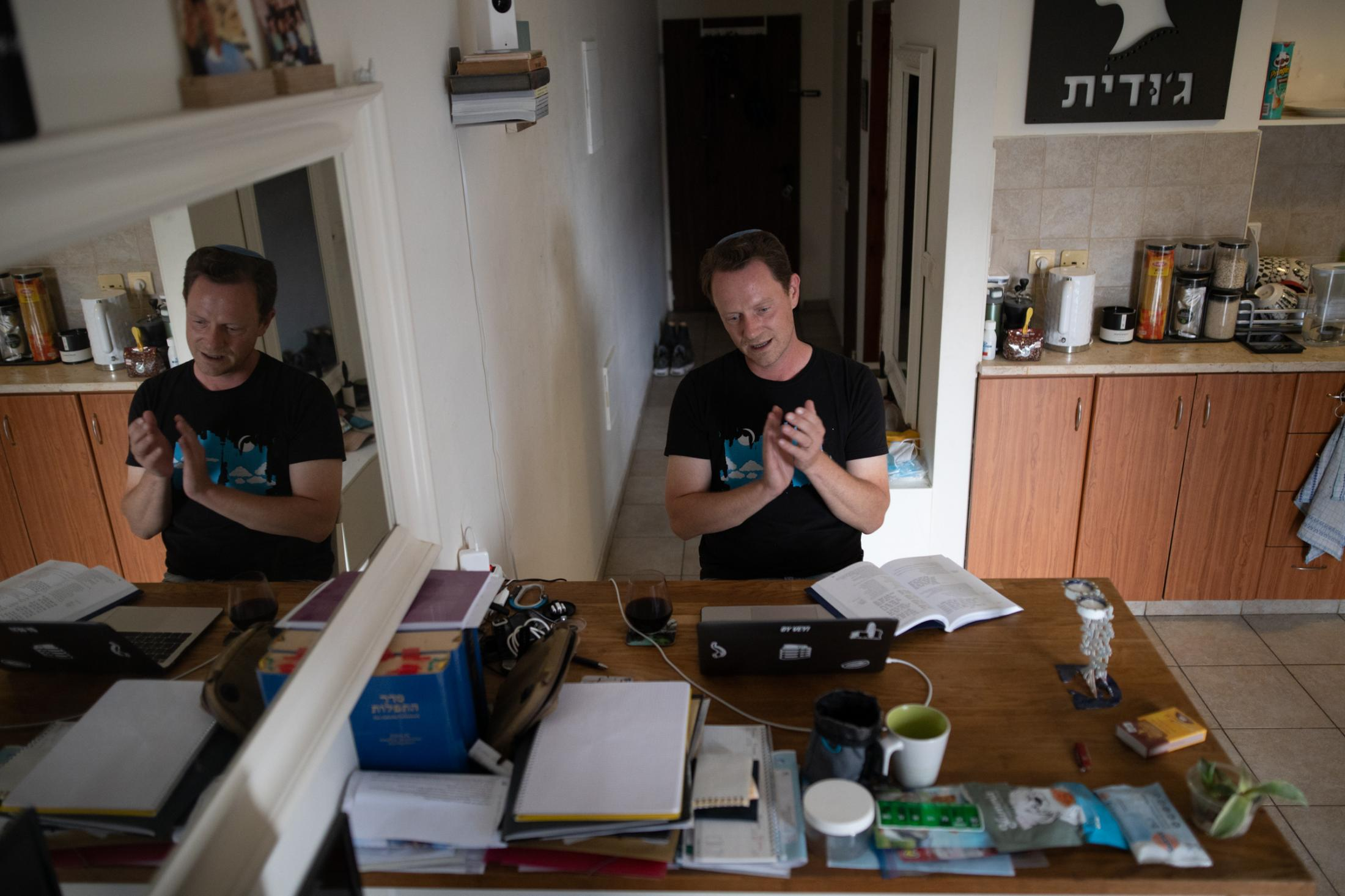"""Christian Hickmann, 43, participates in an online synagogue service in his home in Tel Aviv, Israel, April 10, 2020. """"I appreciate that we have the possibility of online communication. Ten or 15 years ago it would not have been possible in this scope and people would have been much more isolated. It helps to preserve the backdrop of normality. For online services, just hearing the familiar melodies helps pretending that everything continues normally. In the end, it is Potemkin villages, but it helps. However, it is not a long-term solution. Judaism lives from physical encounters and community, which is specifically challenging to recreate virtually."""""""