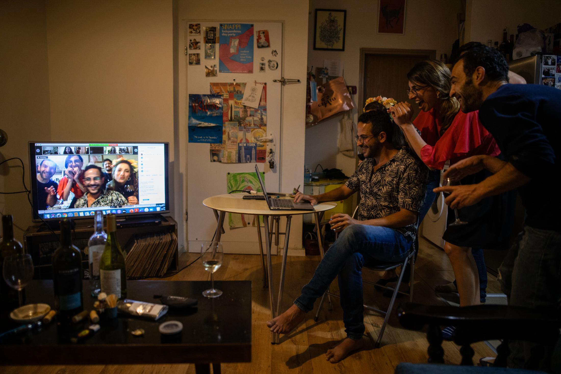 """Idan Teram, 35, Mor, 30, and Gabi, 38 (L-R) dance during an online party at home, in Tel Aviv, Israel, April 24, 2020. Since the lockdown due to Coronavirus, Idan co-founded a facebook group as a platform for virtual parties. """"We miss the hugs, we miss seeing new faces, the music sounds way better in real life. But there are a few benefits. It's pretty convenient, you're staying in your place, you're having a bottle of wine, you're sitting, listening to music and seeing people. And I see people who don't have access to parties in real life - if you live outside of Tel Aviv or if you have kids - these kind of parties can be an answer for people who enjoy music, who want to party, but who won't go to a club. So we actually put the party in your place and have everybody participating - and it works."""" (Idan Teram, 35)"""