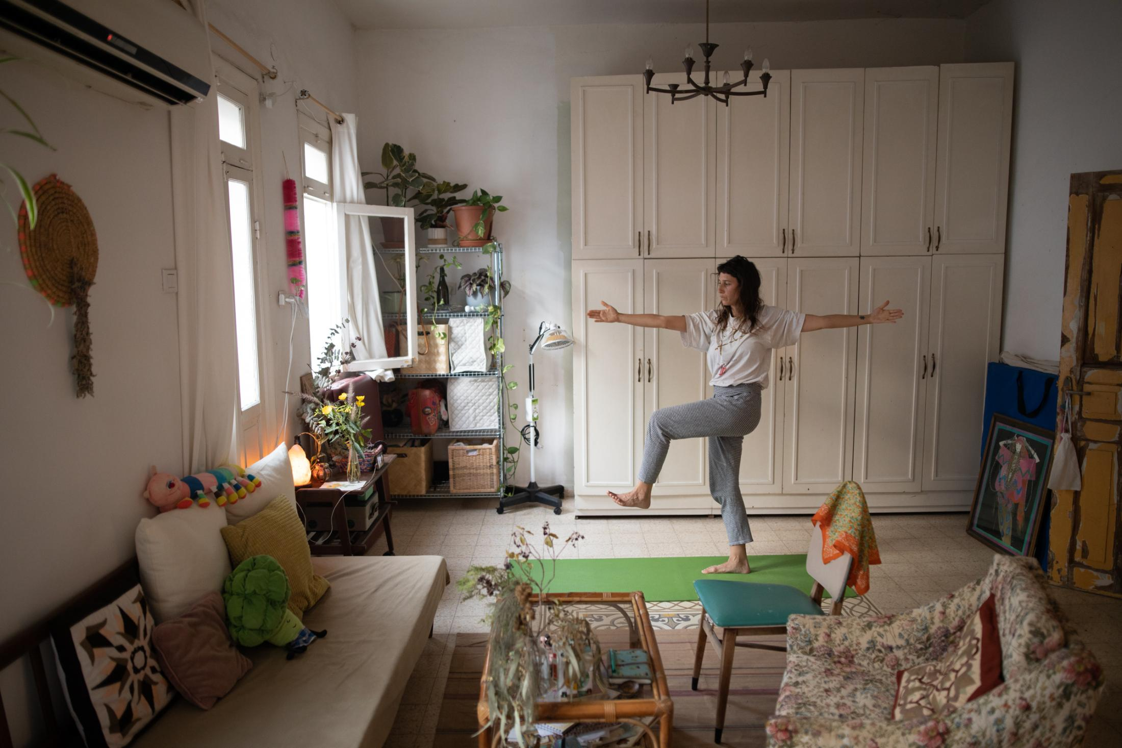 """Yuli Yunger, 34, participates in an online yoga class in her home in Tel Aviv, Israel, April 19, 2020. """"The switch to online was not natural for me. I don't even have a laptop, I have only my cell phone. In the beginning it was weird, and I found it too mechanical. I like the presence of people and of the teacher and that she will move me when I need to be moved. But I got used to it really fast. People are getting used to things, we adjust. And I'm pretty young so I'm adjusting fast. New ideas and new things that you are doing in your life are easy to accept. And it will be easy to leave it as well."""""""