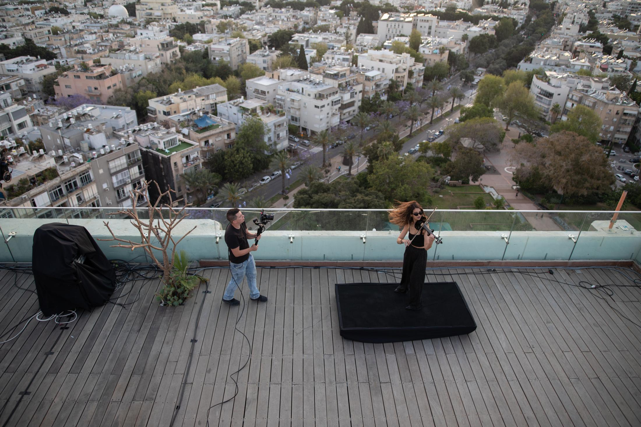 """Violinist Eden Enbar, 28, plays violin during an online party that is broadcasted live via Facebook from the roof of the Tel Aviv municipality building, Tel Aviv, Israel, April 29, 2020. """"It's really weird to perform without a crowd, because we perform for the energy. Now you have to keep up the energy yourself all the time, because you don't have the crowd to do it for you. But since it's already happening for two months we got a bit used to it."""""""