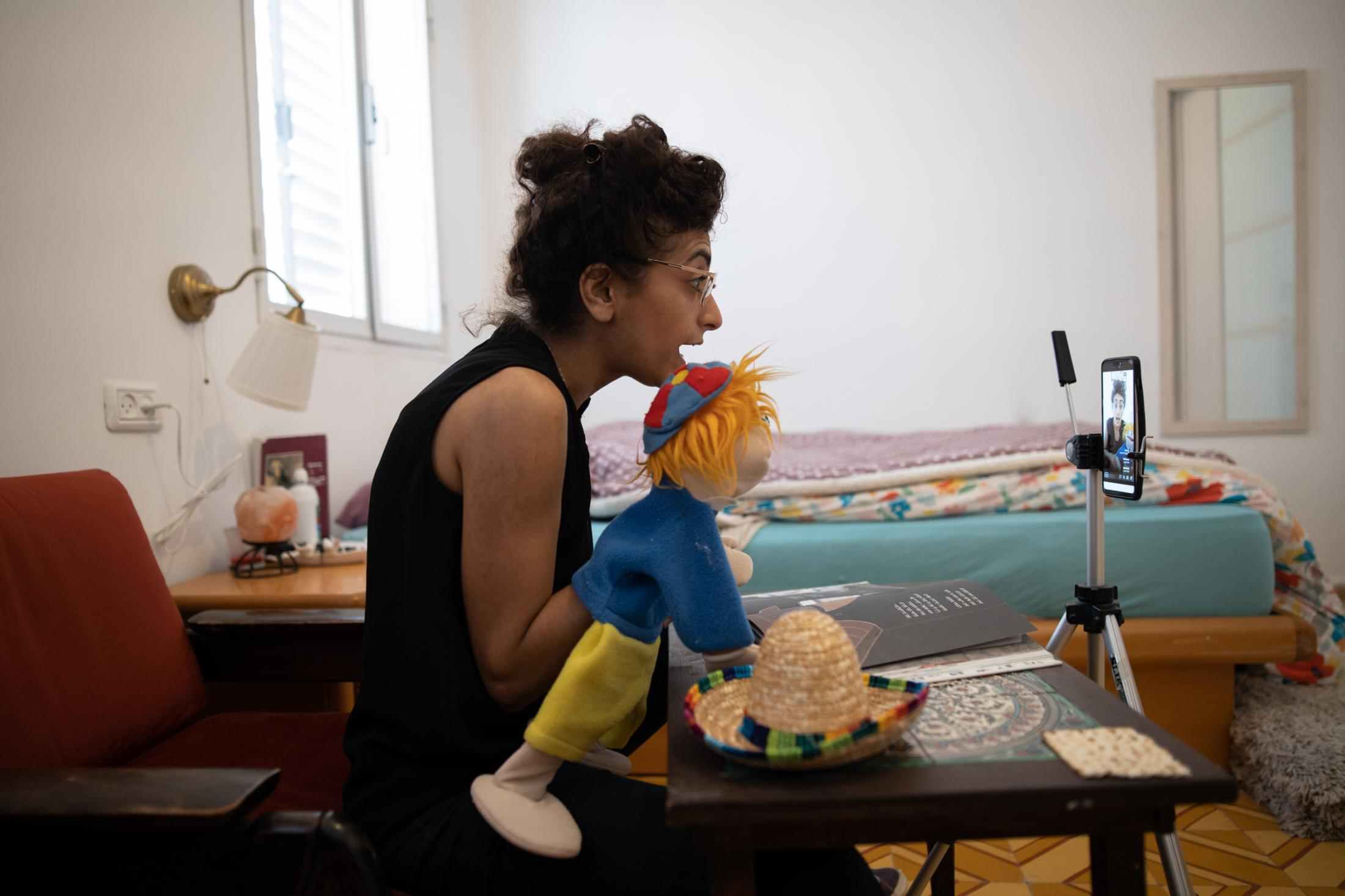 """Actress Ruth Tubi, 35, performs with a doll while doing storytelling for children on Zoom in her home in Tel Aviv, Israel, April 30, 2020. """"Usually I feel the energy of the audience, so it's very different now. This is why online I included the puppet, which makes me feel like somebody else is with me. In storytelling for children, you usually stop in between to ask them how they feel. Now the puppet gives me the answer instead of the children."""""""