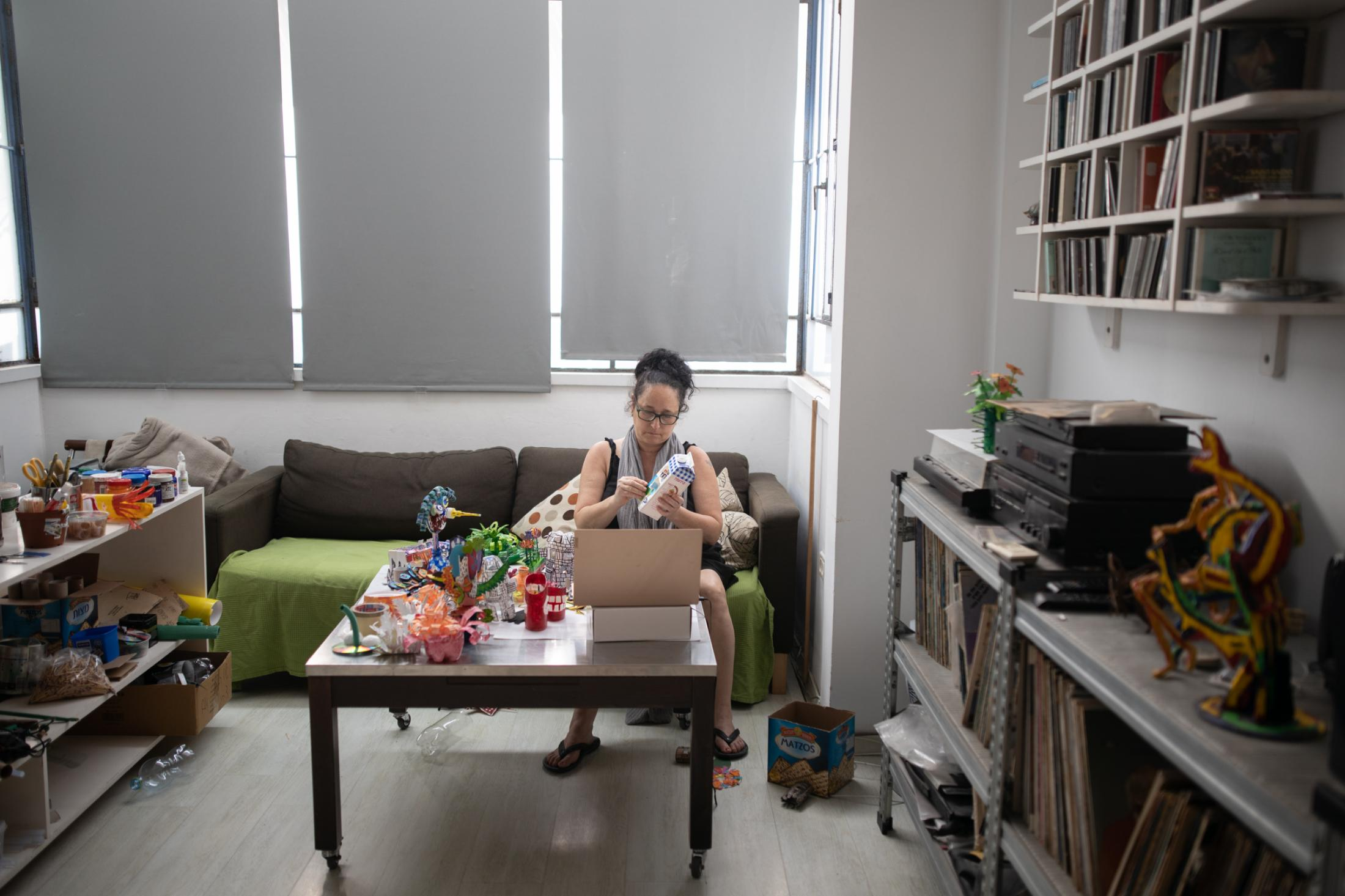 """Art teacher Yael Yaari, 53, creates art from recycling materials as part of an online class for children on Zoom in her home in Tel Aviv, Israel, April, 20, 2020. """"I changed my whole perspective. I mostly work in my apartment now, which has basically become my studio. I spend all day here, which means I cook here, I work here, I have my breaks here - There is something about it, my life and my art became intertwined. I like it."""""""