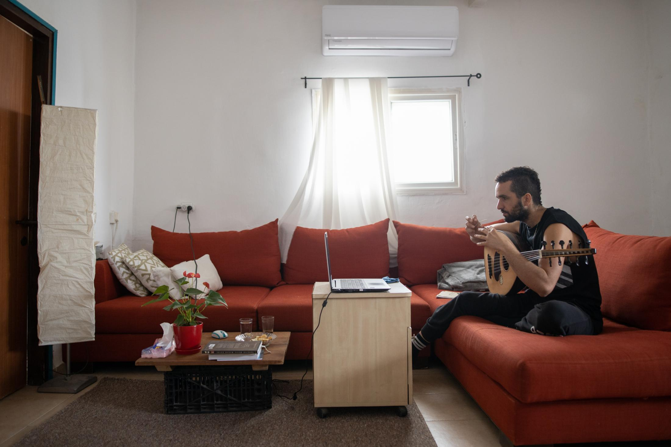 """Musician David Cohen, 32, plays on his Oud while giving an online lesson of Arabic music via Zoom in his home in Tel Aviv, Israel, April 24, 2020. """"Teaching music online is very tricky. With 'Zoom' there is a delay. So you cannot teach a rhythm, for example. I cannot see how my students' hands work and I cannot adjust them. Getting used to being apart from people, and then starting to learn how to meet each other again, but in Zoom - it's not a relationship, it's not the way to learn or to teach, it's nothing."""""""