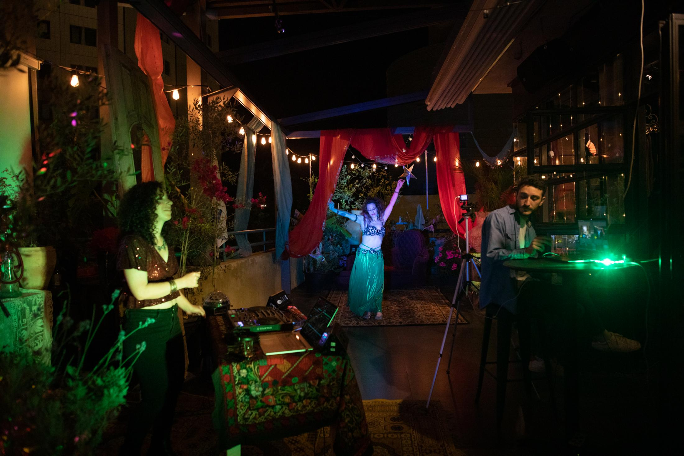 """Dancer Ella Greenbaum (center), 41, and DJ Neta Haimovich (left), 35, perform during a Mimouna event, a traditional Moroccan celebration, that is broadcasted live via Facebook from the Inta Lounge Bar in Tel Aviv, as part of an initiative by the Tel Aviv municipality to provide free online events during the coronavirus lockdown, Israel, April 15, 2020. """"It's amazing to see that this communication is working. It can't replace the sensual authentic feeling when you get in a real live show, but it's better than nothing. """" (Ella Greenbaum, 41, dancer) """"It's hard as a DJ not to get responses from the crowd. When I'm preparing for a party, I never know what I'm going to play. I'm just looking at the crowd and the way people react to different kinds of music and that is how I know what to play. But in the medium that we picked (Facebook live) I couldn't feel the crowd, so you have to be your own party."""" (Neta Haimovich, 35, DJ)"""