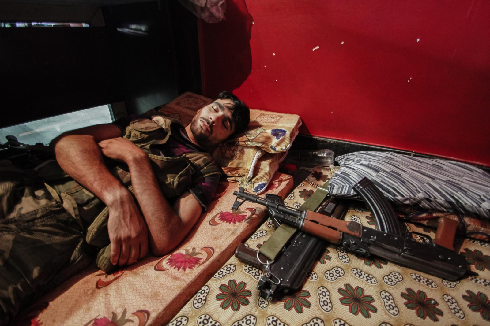 A member of the Free Syrian Army sleeps in a business in Aleppo that has turned into a makeshift headquarters for the FSA in between fighting Assad's forces on August 22, 2012.