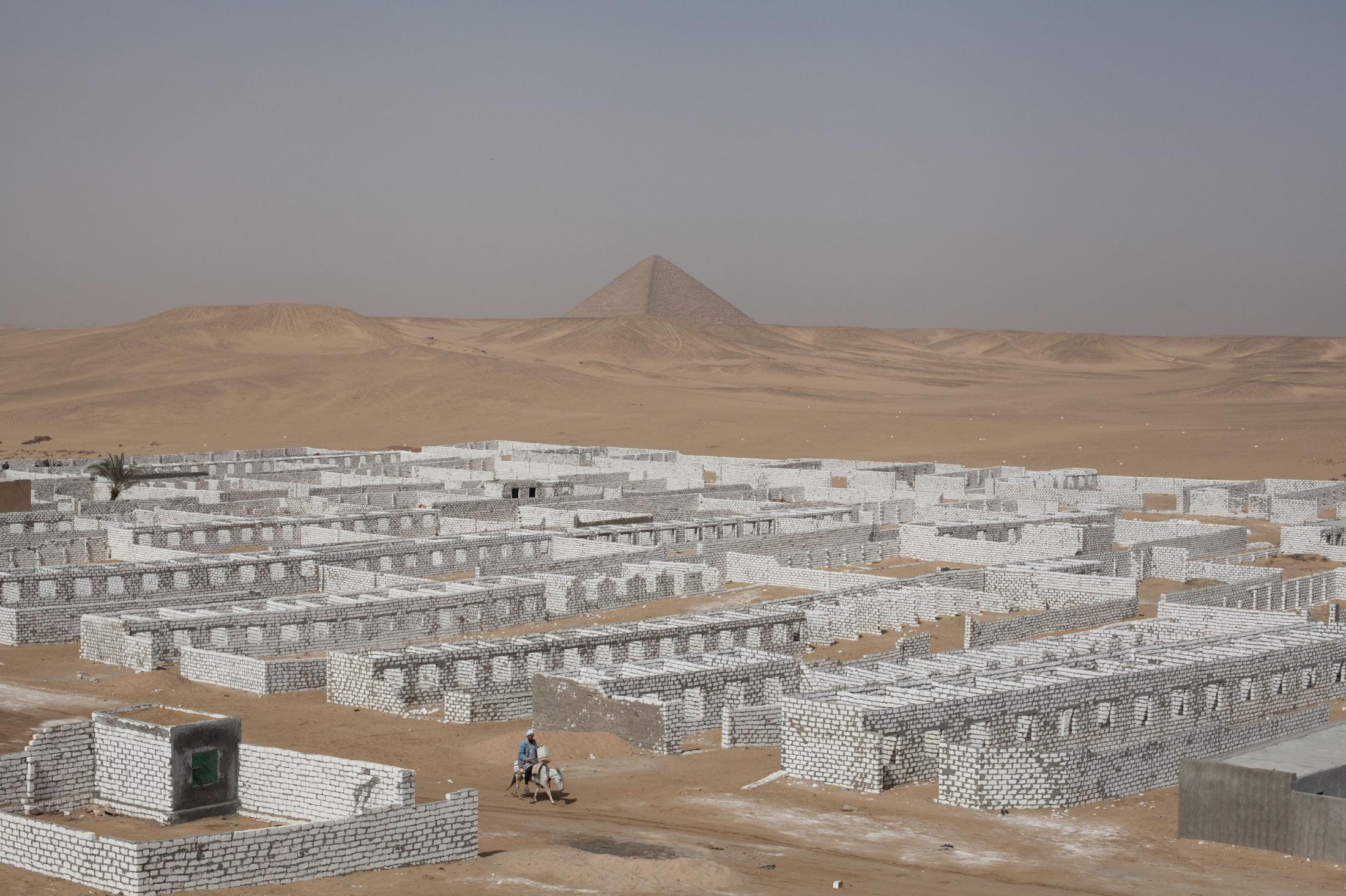 A man on a donkey passing through a white stone wall cemetery.  Sneferu's first smooth sided Red Pyramid can be seen in the distance.