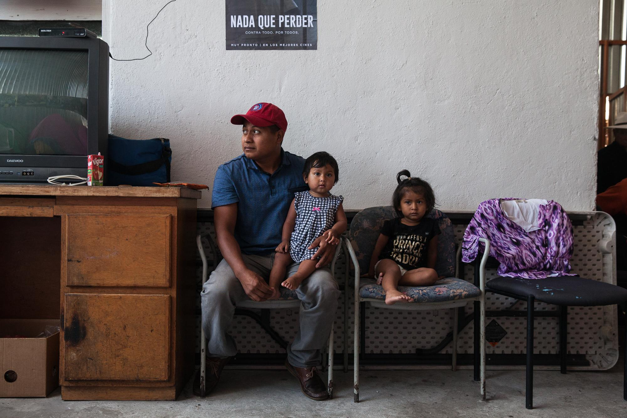 After sleeping their first night in a tent at Juventud 2000 shelter in Tijuana, MX, a family sits near the entrance of the shelter on April 25, 2018.