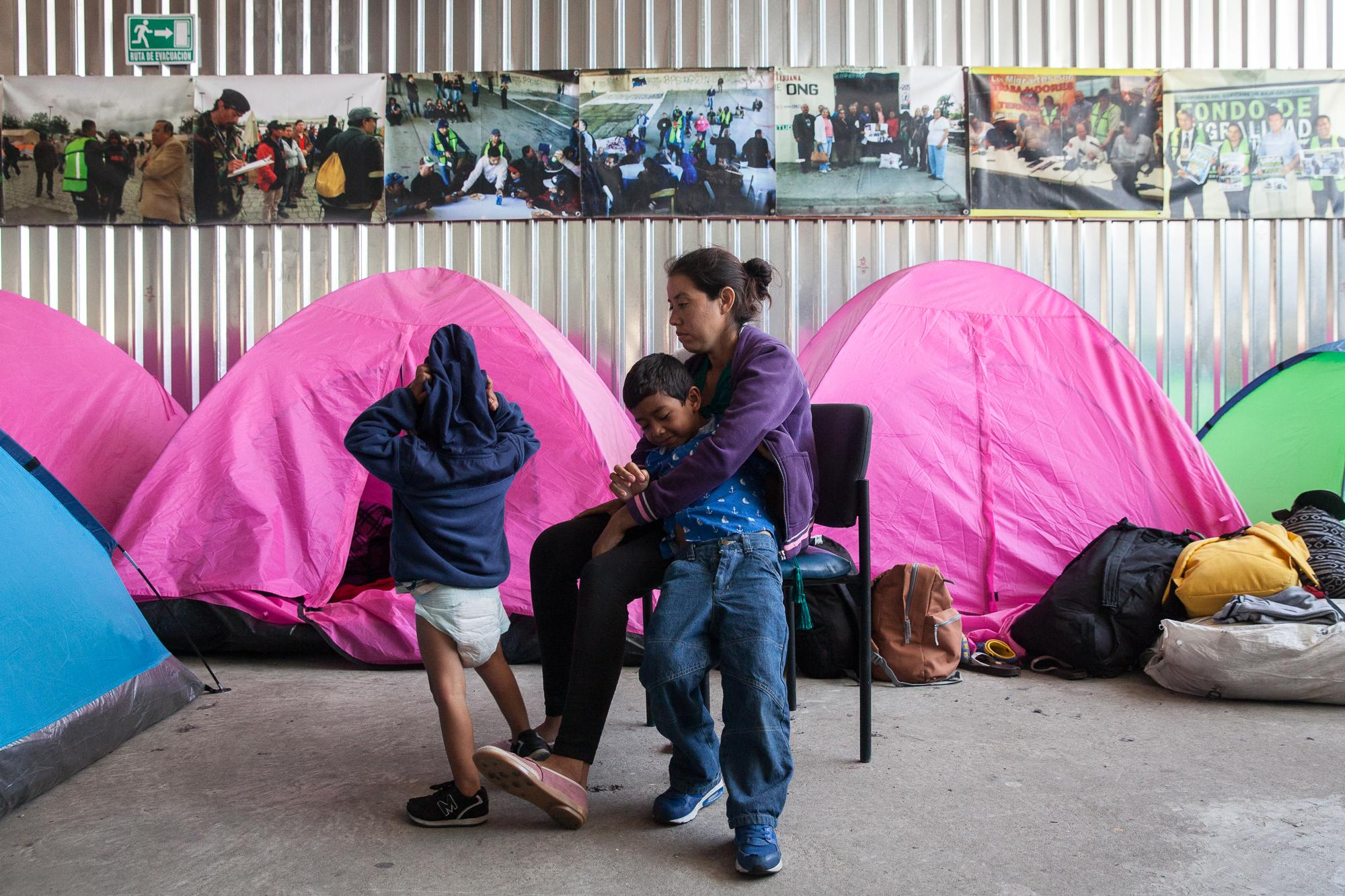 Gabriela Hernandez, a pregnant mother of two, sits in a room filled with tents at Juventud 2000 shelter in Tijuana, MX, with sons Omar, 6 years old and Jonathan 2 years old on April 25, 2018. Hernandez left her husband after suffering domestic abuse. They fled Honduras when gang members threatened to kill her son Omar because they couldn't find her ex. They said she had 12 hours to give up her ex or else. She decided to take her children and travel with the migrant caravan through Mexico.