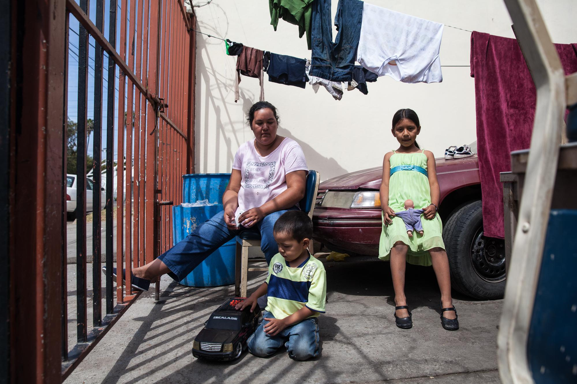 A family sits outside of the Viña de Cristo shelter on the edge of the red-light district in Tijuana, MX, on April 26, 2018.