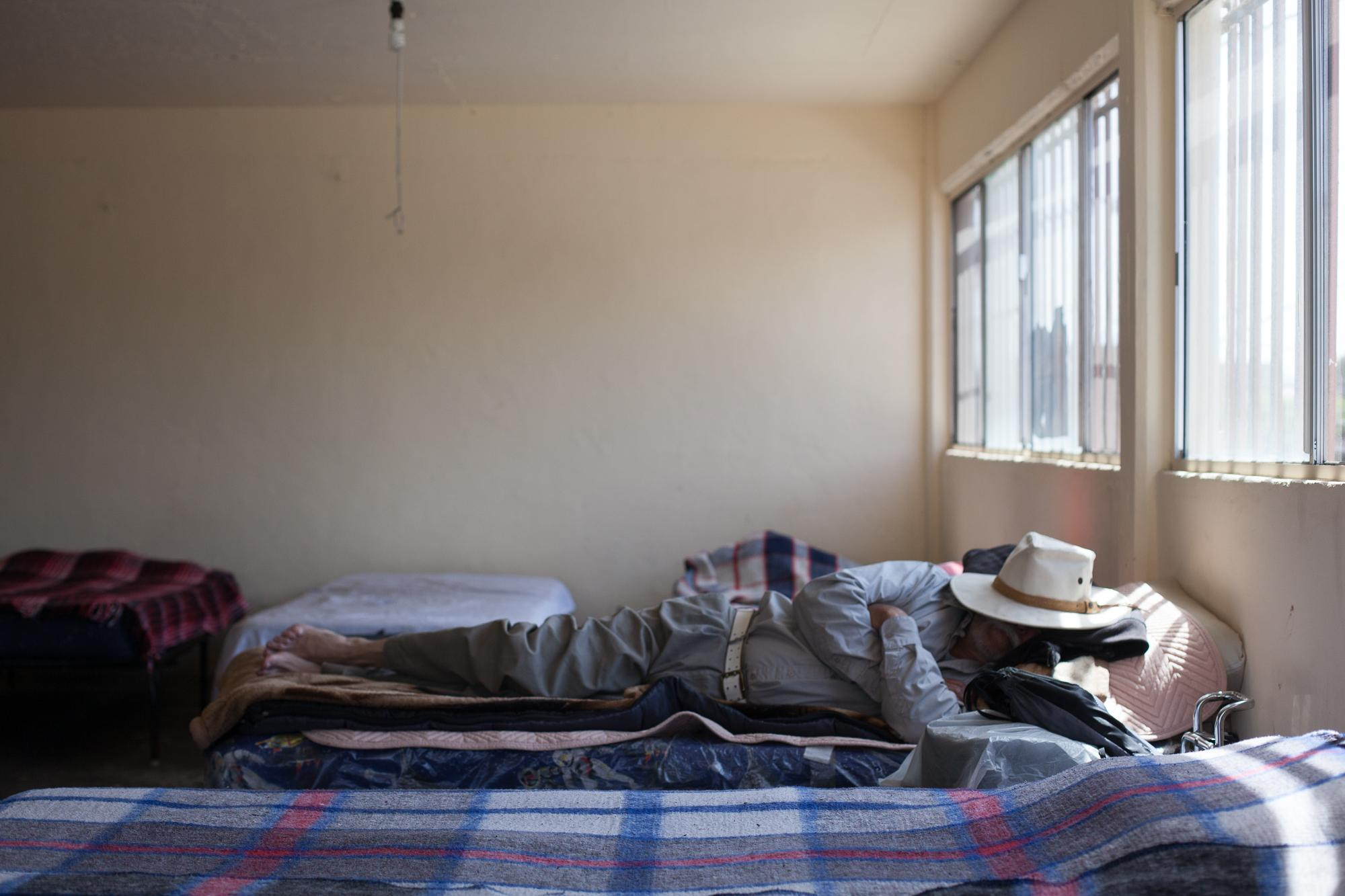 An older man sleeps in the morning at a shelter in Tijuana, MX.