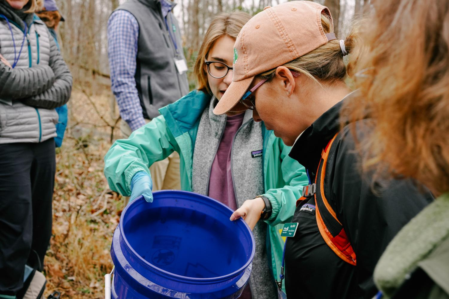 Student Biology leader and senior at Sweet Briar College assists Mike Hayslett with lecturing and presents unique salamander spices to the group as an example of the unique wildlife found in vernal pools, 2020.