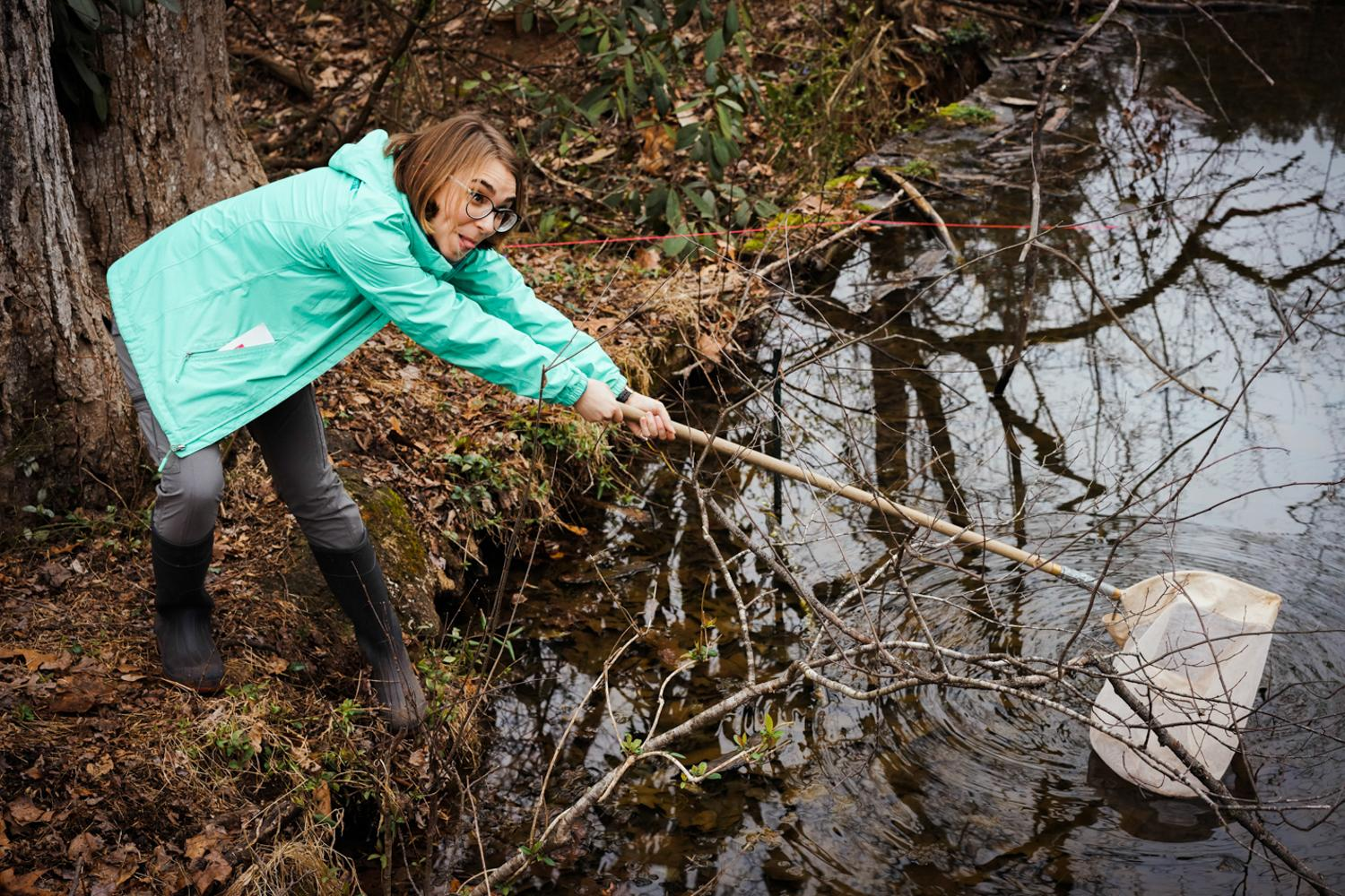 Teaching assistant and head of the student body biology group at Sweet Briar attempts to reel in some of the crawfish native to this vernal pool, 2020.