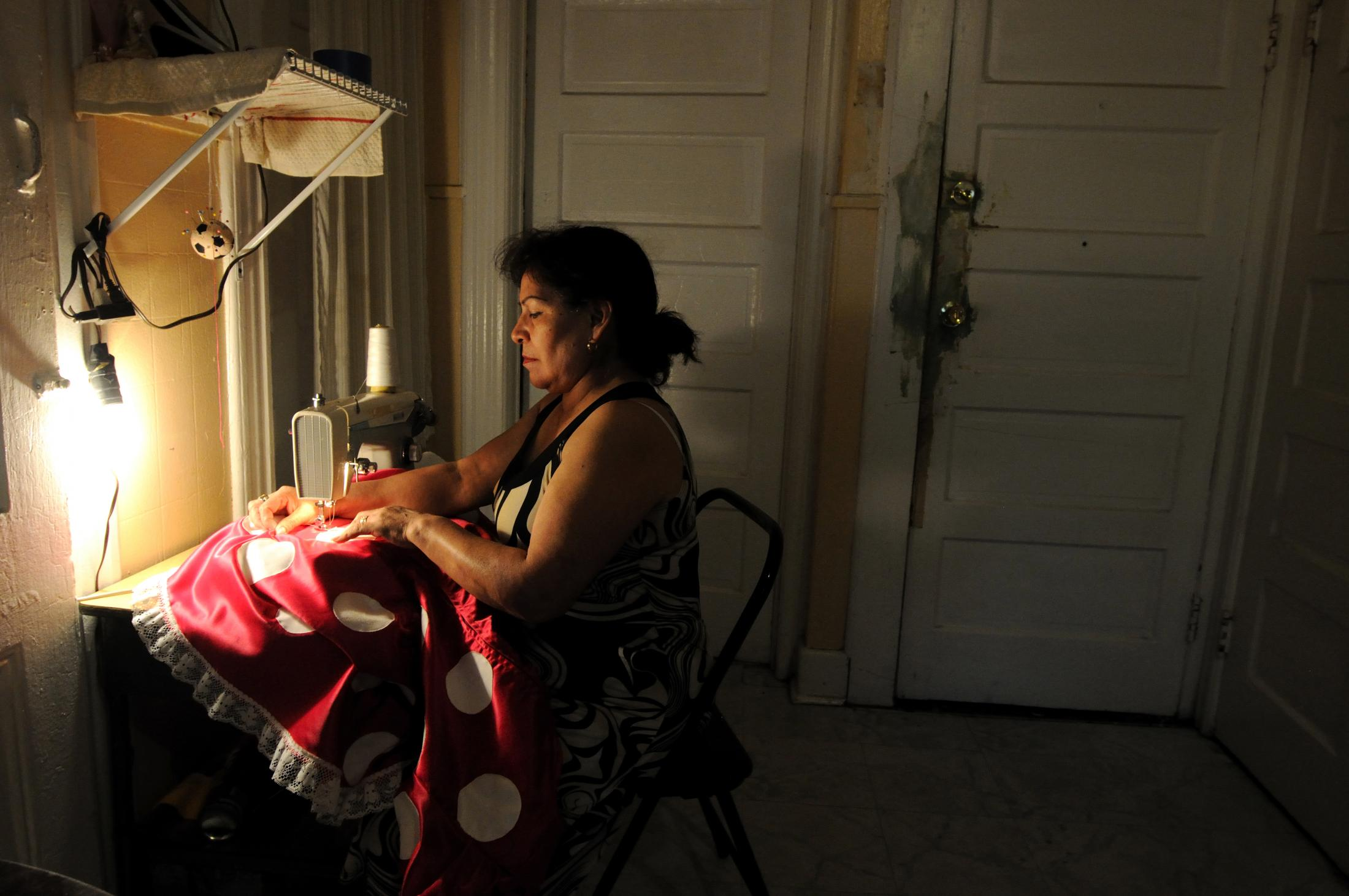 New York, UNITED STATES Doña Berta,55,from Mexico repairs her Minnie Mouse costume at her house in New Jersey. 2013 Joana Toro.