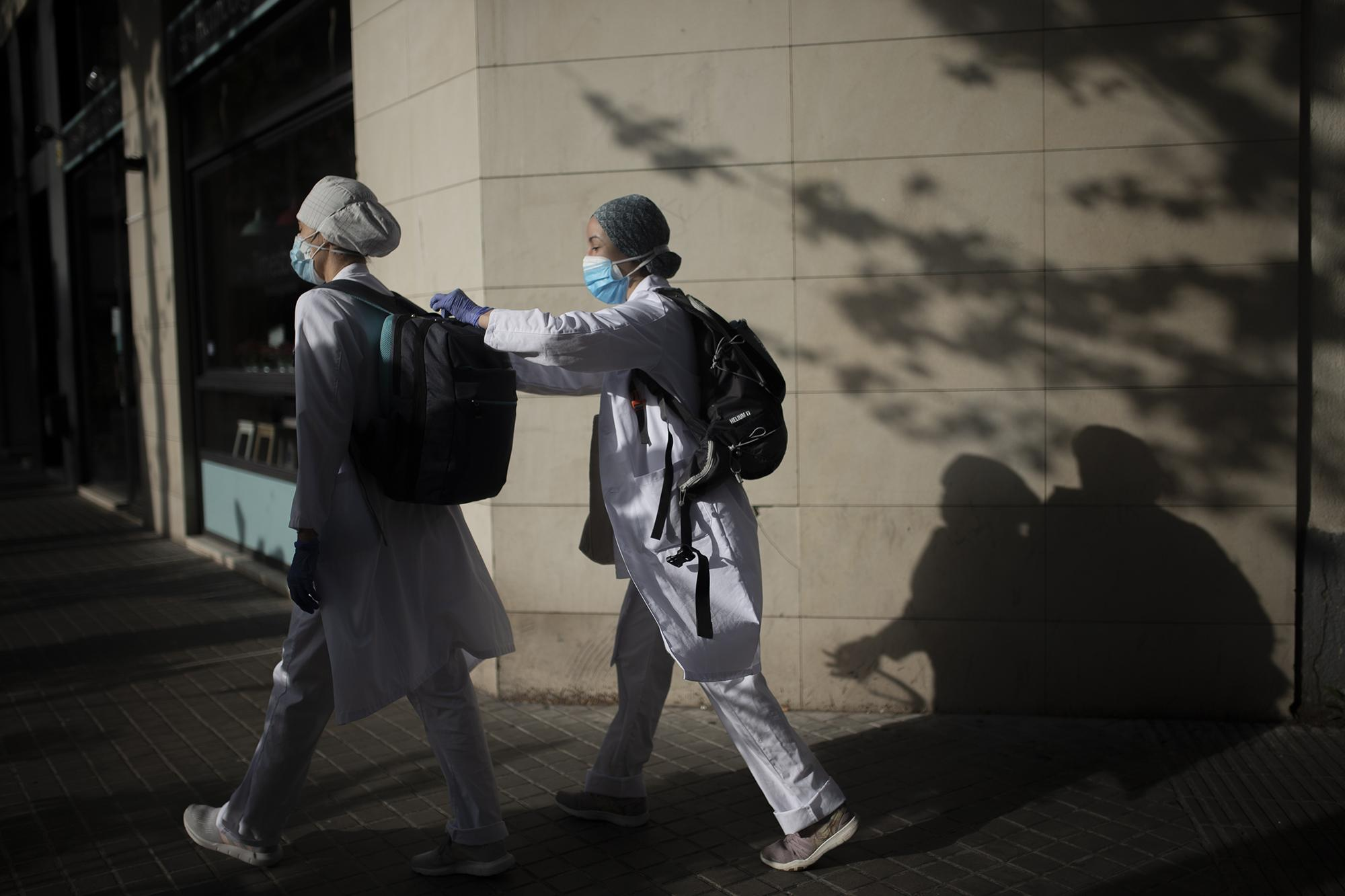 Nurses Sumia and Judit walk to patients homes during the COVID-19 virus outbreak in Barcelona, Thursday , April 16.