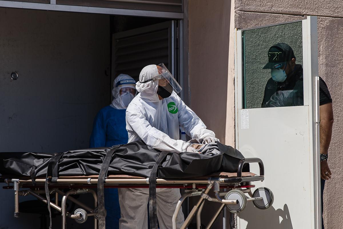 A man identifies his 74 year old father behind a protective panel who died of coronavirus-related complications at General Hospital No.1 in Tijuana, Mexico on May 6, 2020.