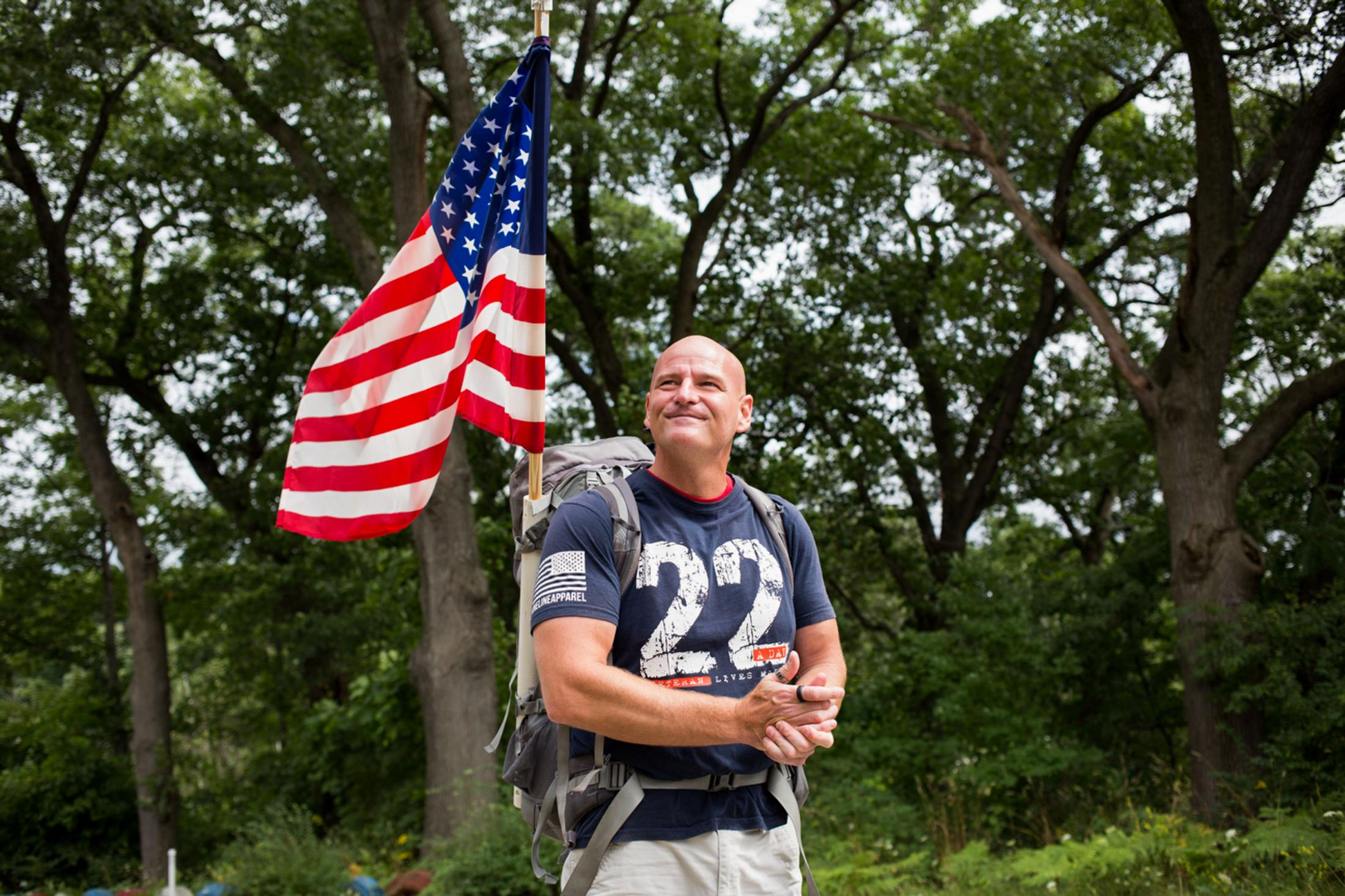 Marty Willis, a U.S. veteran, carries an American flag on his back to raise awareness for veterans who have committed suicide in Muskegon, MI.