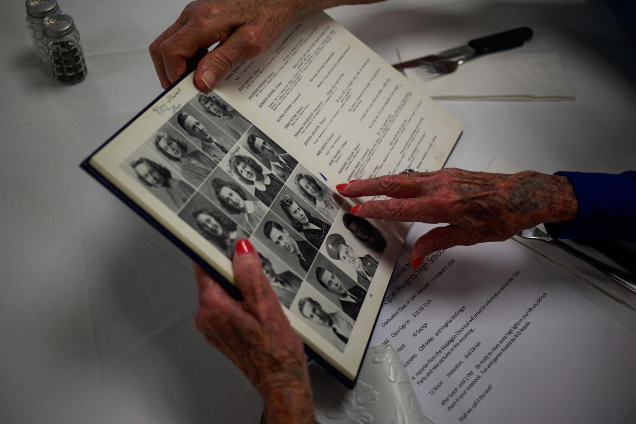Two classmates look at their high school yearbook during the Muskegon Heights High School Class of 1943 banquet. Fifteen surviving members celebrated and reminisced on their high school years.