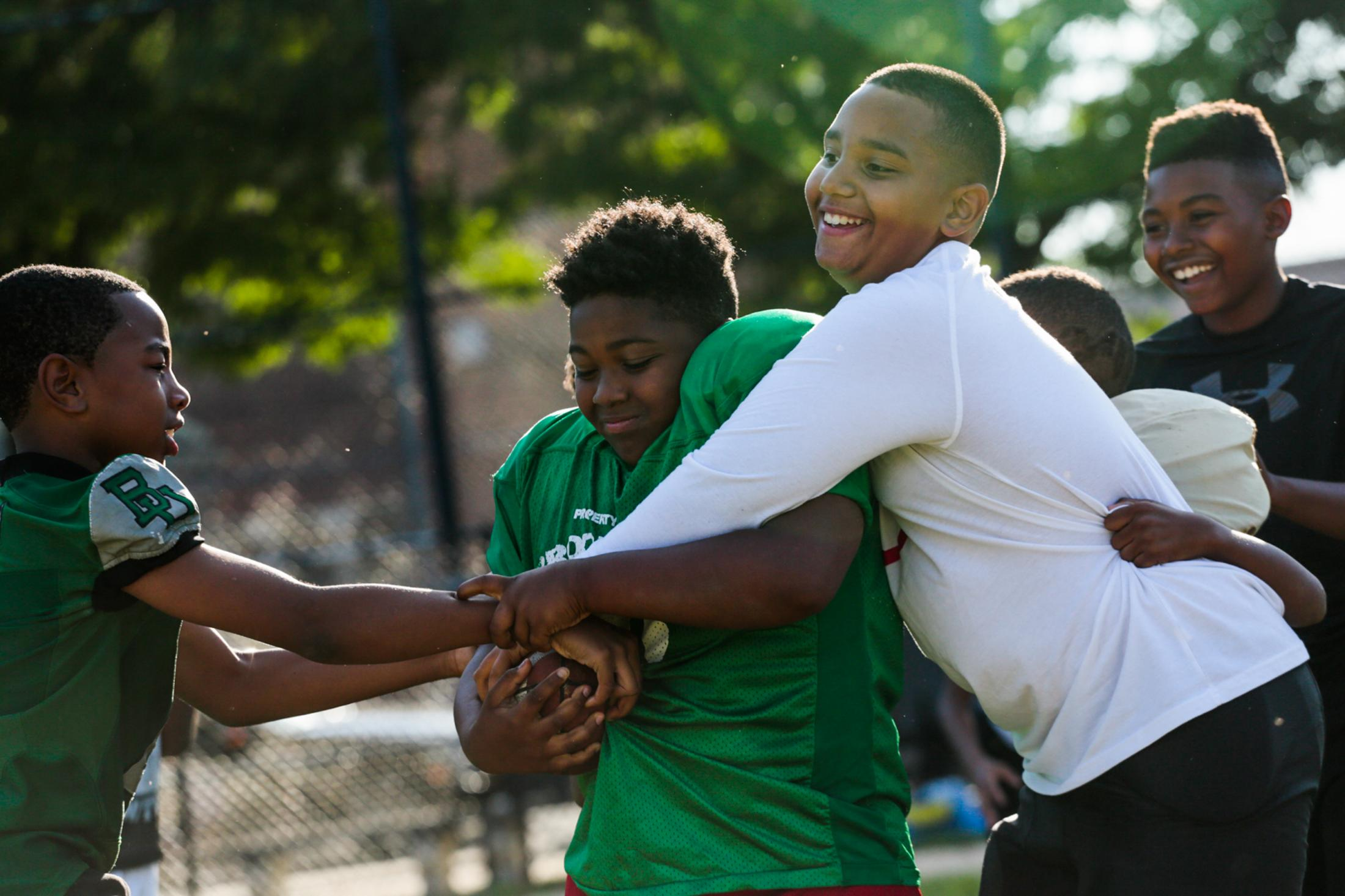 From left to right: Reid Jones, Josaih Howard, Asani Low, and Dollar Beamon try to tackle a football during practice at the Floyd Patterson Field in Brownsville, NY. The Brooklyn United Youth Football League received a $5,000 Play Ball Grant which will be used to fund and develop football programs for Brownsville youth.