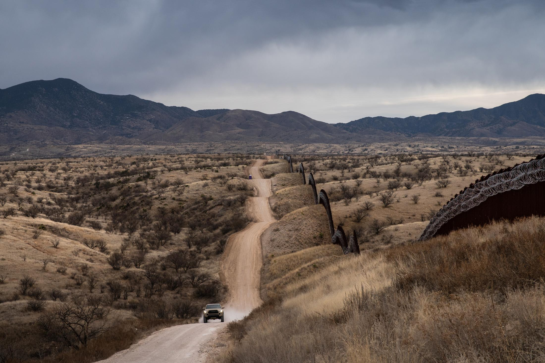 A truck speeds by the US border fence covered in barbed wire concertina separating the US and Mexico, at the outskirts of Nogales, Arizona, on February 9, 2019.