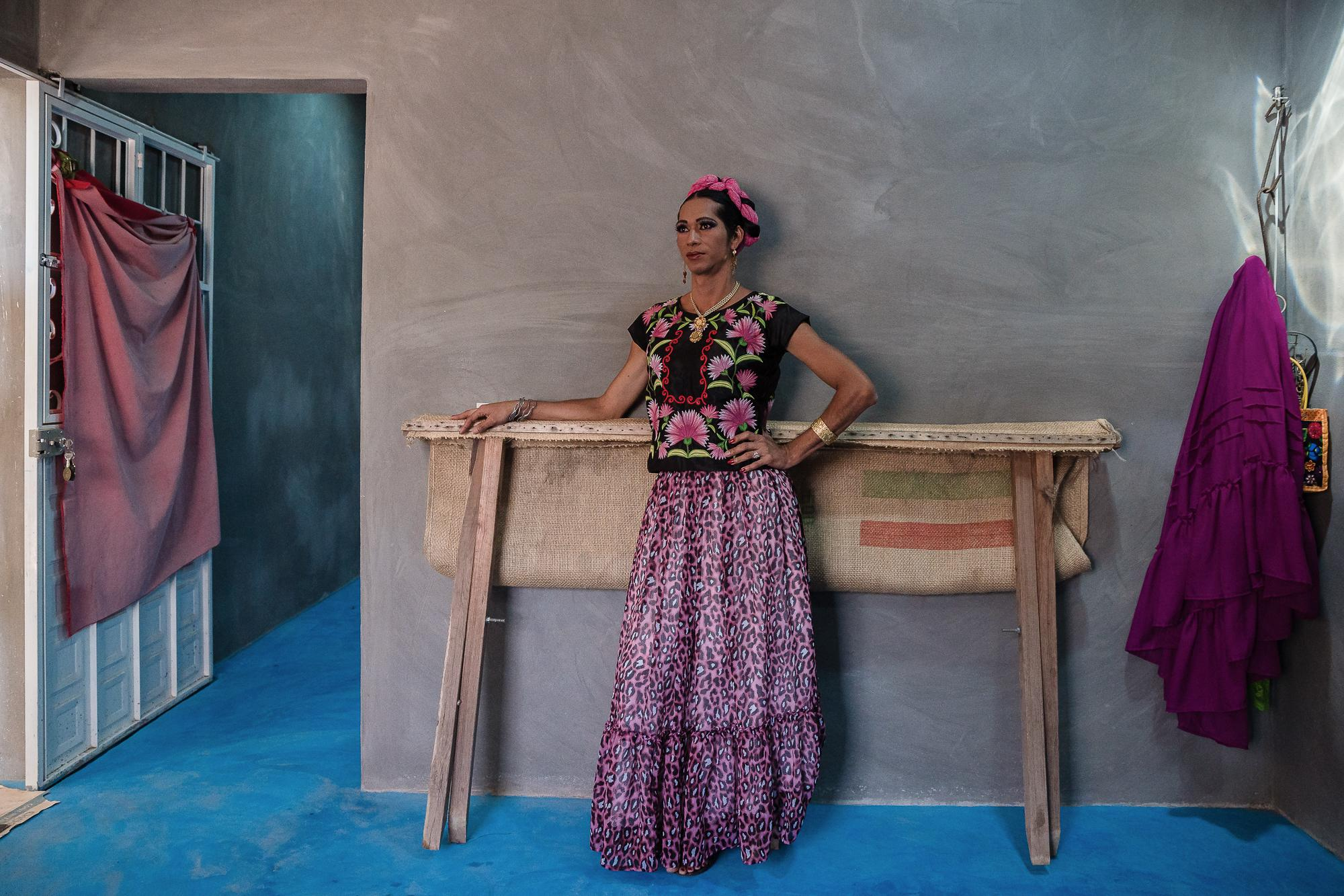 Estrella poses for a photo wearing a traditional huipil garment with colorful flowers.
