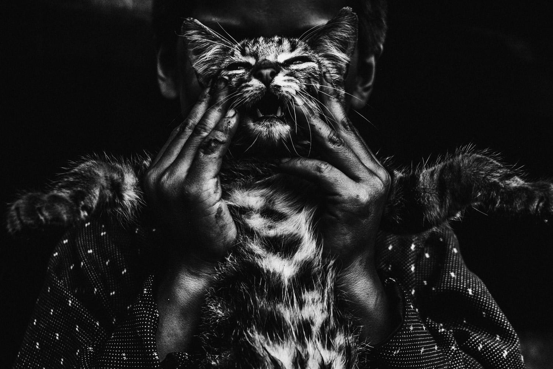 Erasmo toma a su gato mientras juega con él.