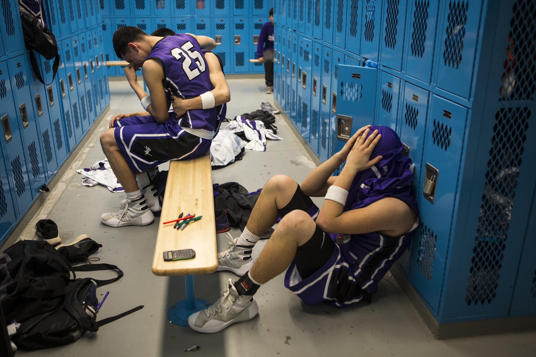Joaquin Romero hugs a teammate, as Javante Chavez sulks on the floor, after the Santa Rosa Lions were eliminated from the state championship competition by Tucumcari on March 9, 2016. The Lions were defeated 65-63.