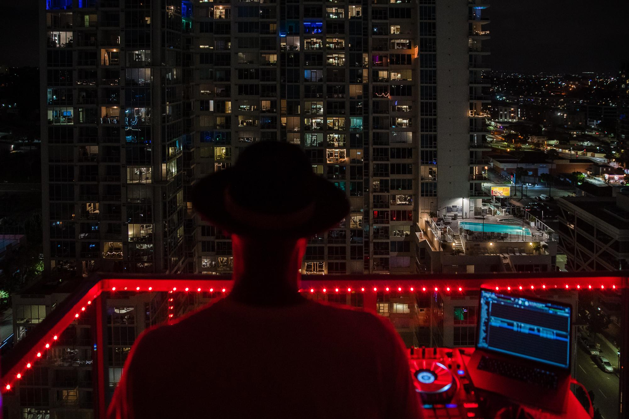 DJ IAMNOEL plays his set on a balcony in downtown San Diego on April 11, 2020.