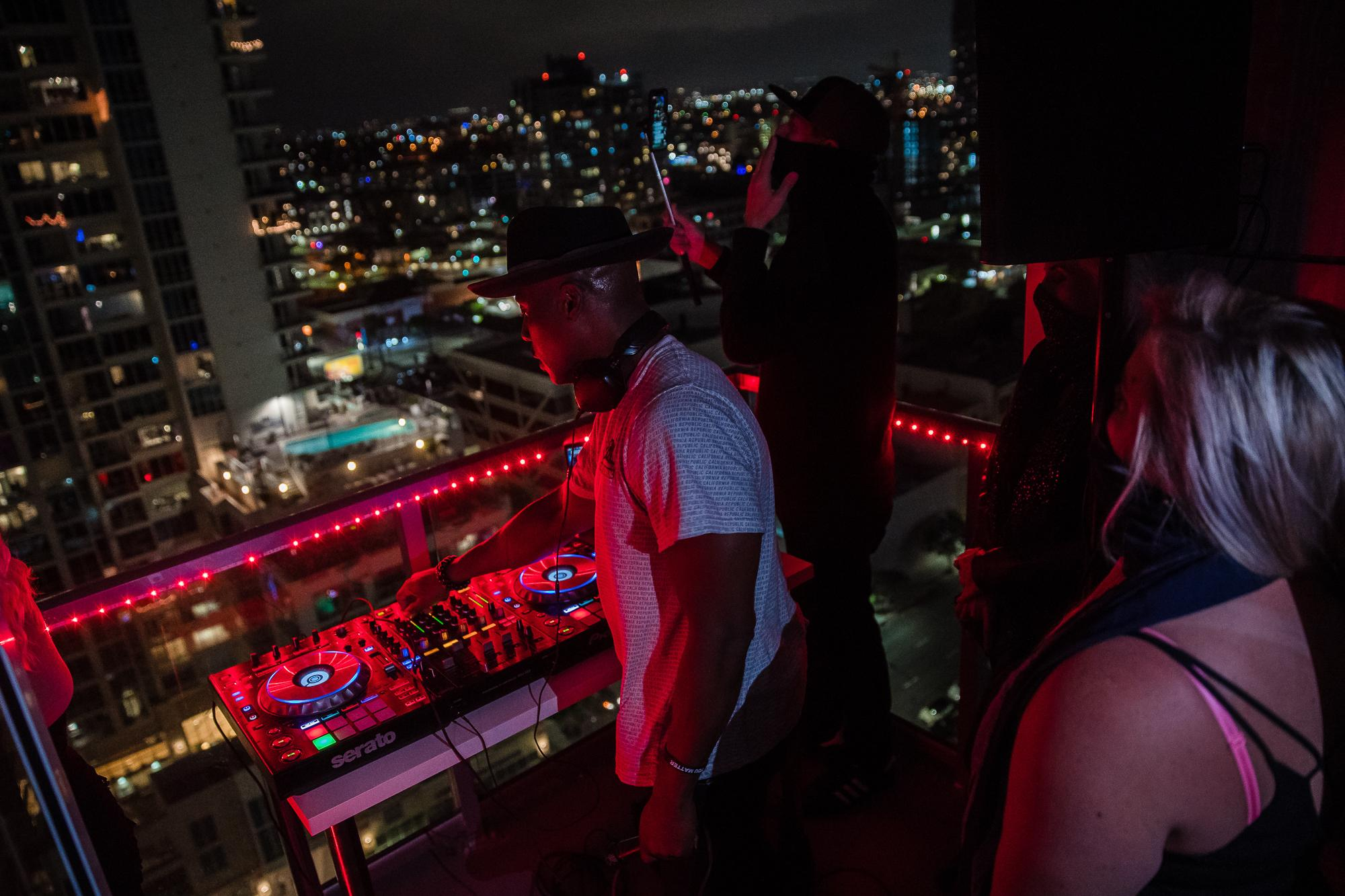 DJ IAMNOEL can be seen with a friends wearing bandanas on their faces while he plays his set on a balcony.