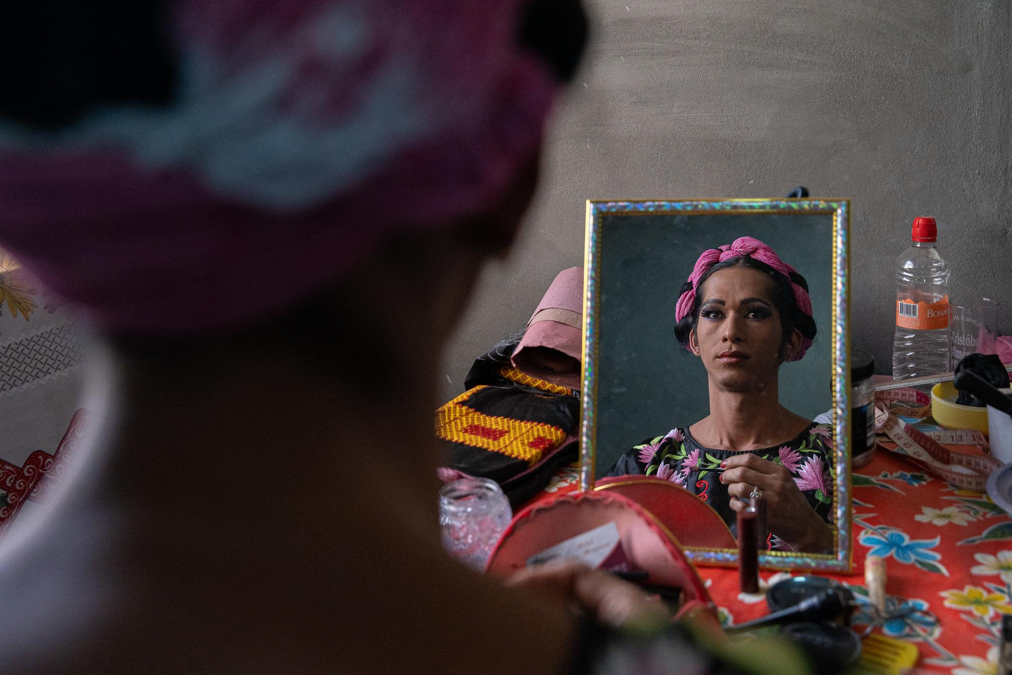 Estrella looks in the mirror after she applies make-up in her home.