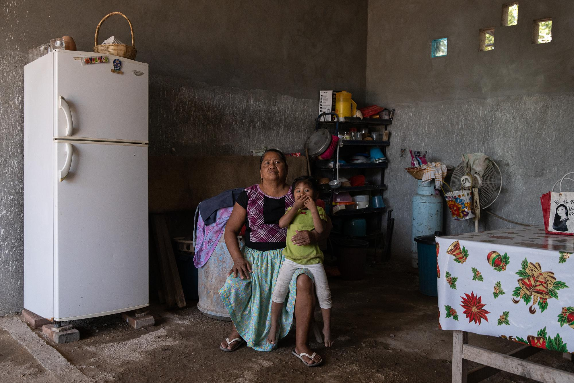 Maria de Jesus Guerra the mother of  Estrella waits for her to get ready while sitting in their kitchen.  Many muxe have been known to care for their ageing parents, some even say it's a blessing to have a muxe son so they can help out at home.