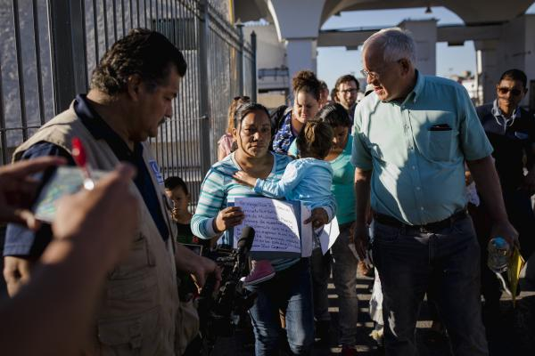 Angelica of Michoacán walks through the El Paso del Norte Port of Entry with Ruben Garcia of Annunciation House, a migrant aid agency, at the international boundary line to cross into the United States to seek asylum for her and her grandchild on June 20, 2018.