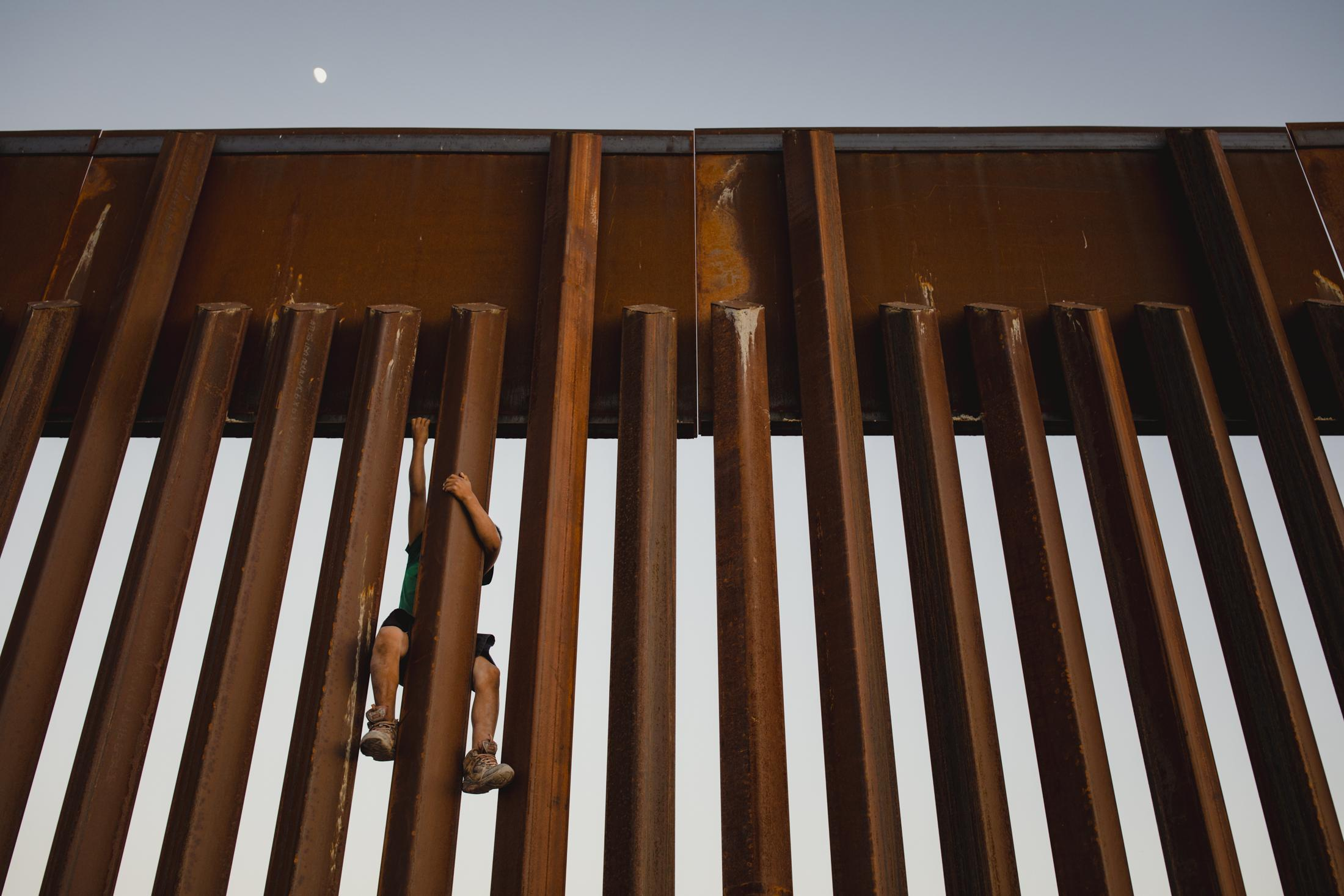 A young boy climbs the Mexican and United States border fence in Sunland Park, New Mexico in the summer of 2018.