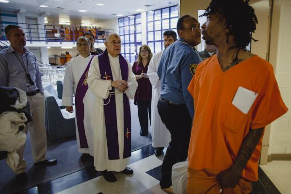 "An inmate enters his pod where the Archbishop of Santa Fe, Michael Sheehan, blessed prisoners on Ash Wednesday at the Metropolitan Detention Center in Albuquerque, New Mexico. ""You couldn't come to me today in the cathedral, so I came to you,"" said Sheehan."