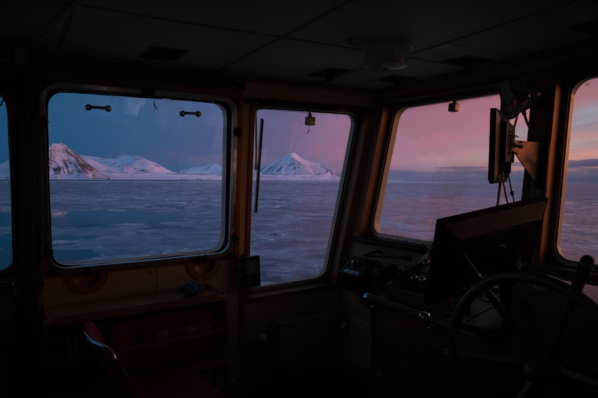 A March sunset glows through the bridge of an expedition vessel traveling the coast of Svalbard. In another month, the midnight sun will return, making March an ideal time of year for photography due to the colors of light.