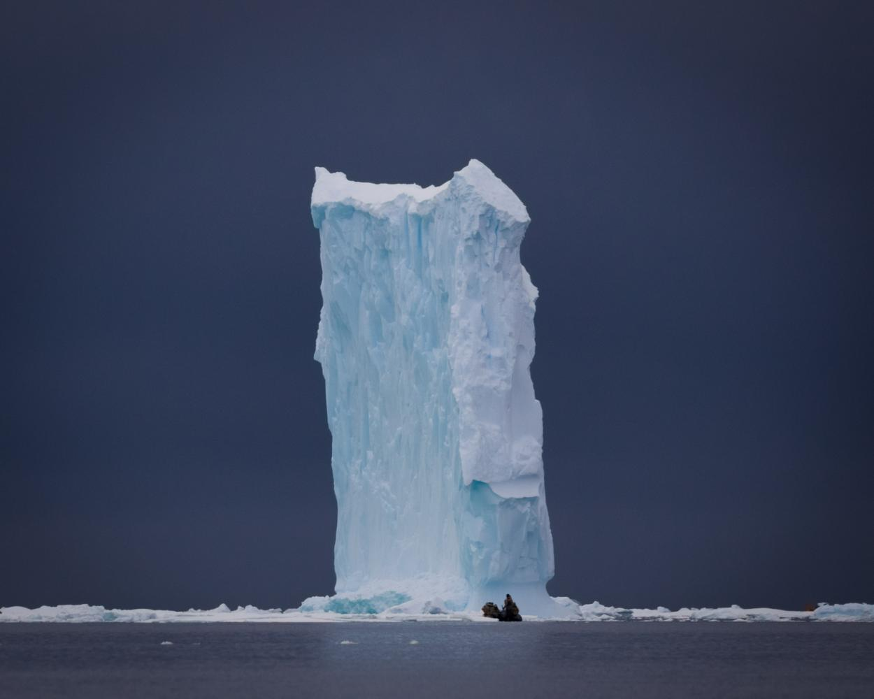 An expedition guide approaches a massive iceberg in Wilhelmina Bay, Antarctica.