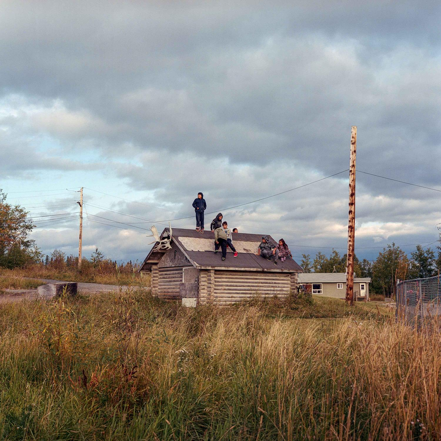 September 13 2016. Children play on the roof of an old cabin in the community of Cross Lake, home to the Pimicikamak Cree Nation in Northern Manitoba, Canada. Regulation from the Jen Peg dam has drastically impacted the community through drastic and sudden fluctuations in water level causing substantial long-term erosion, difficulty navigating the water by boat, and dangerous ice conditions for travel in the winter months. The cumulative impacts have devastated wildlife, fish populations, and eroded a cultural way of life. Cross Lake has dealt with a rash of youth suicides in recent years, which brought the community into the national spotlight. In 2016, 5 youth killed themselves and there were 140 expressions of desire or suicide attempts, that year they had the highest suicide rate in Canada.