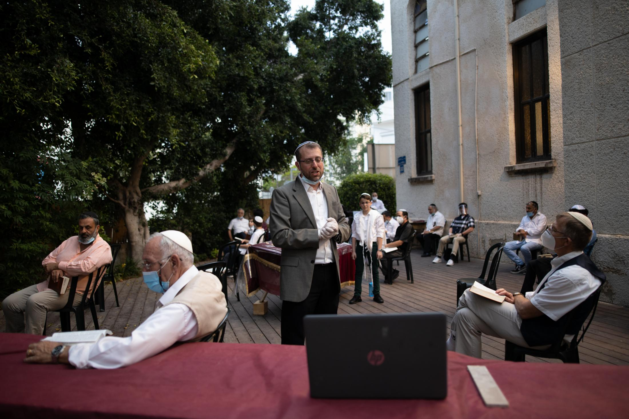 Rabbi Ariel Konstantyn (center) speaks to participants watching a Facebook live broadcast of his Kabbalat Shabbat service in the yard of the Tel Aviv International Synagogue, Israel, May 15, 2020.