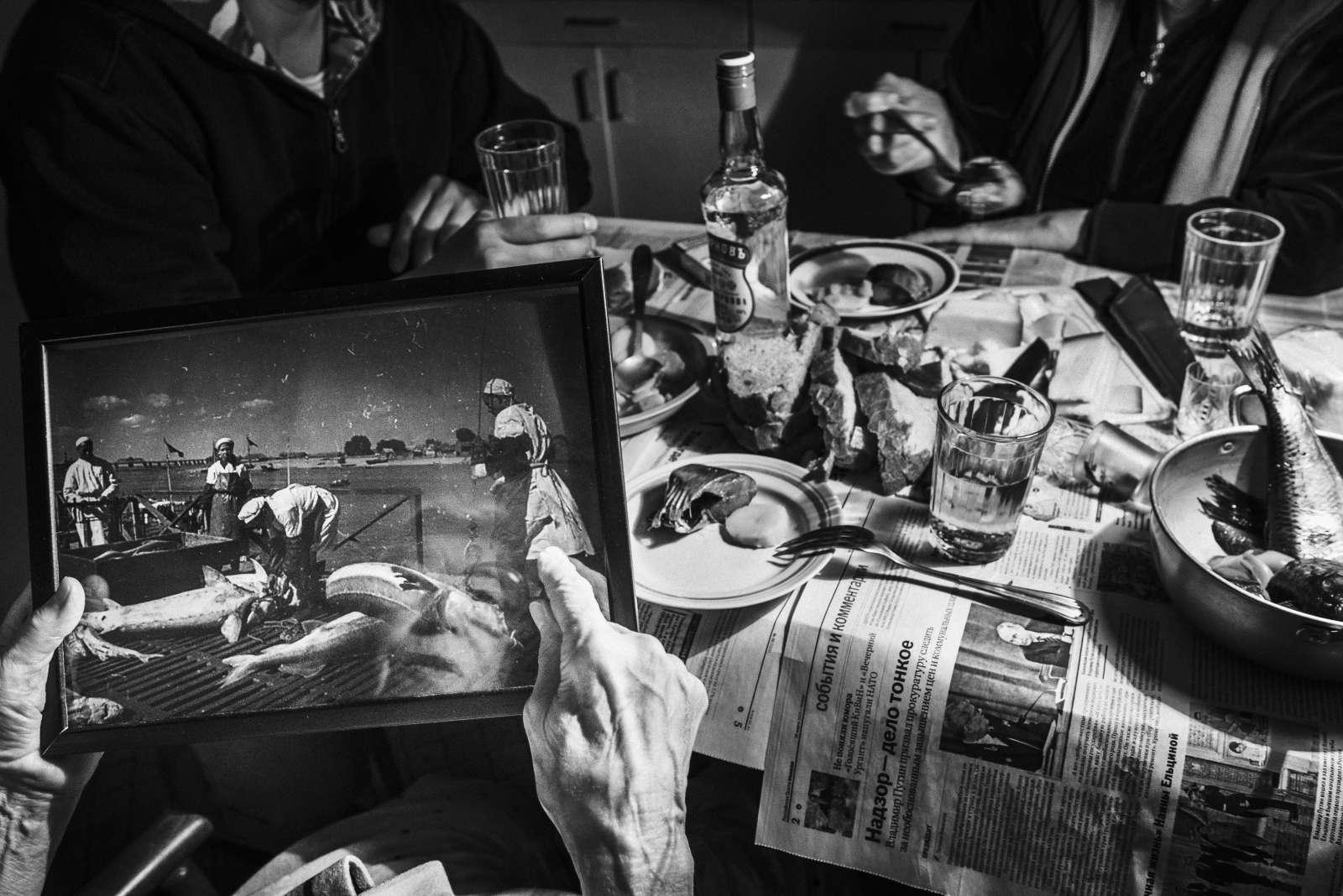 Galina, senior living in Moscow, Russia, shows a photograph taken more than 50 years ago of the fishermen working. She remembers there was a lot of big fish. Here first love was a fisherman. April 2017 Moscow. Russia. © Stoyan Vassev