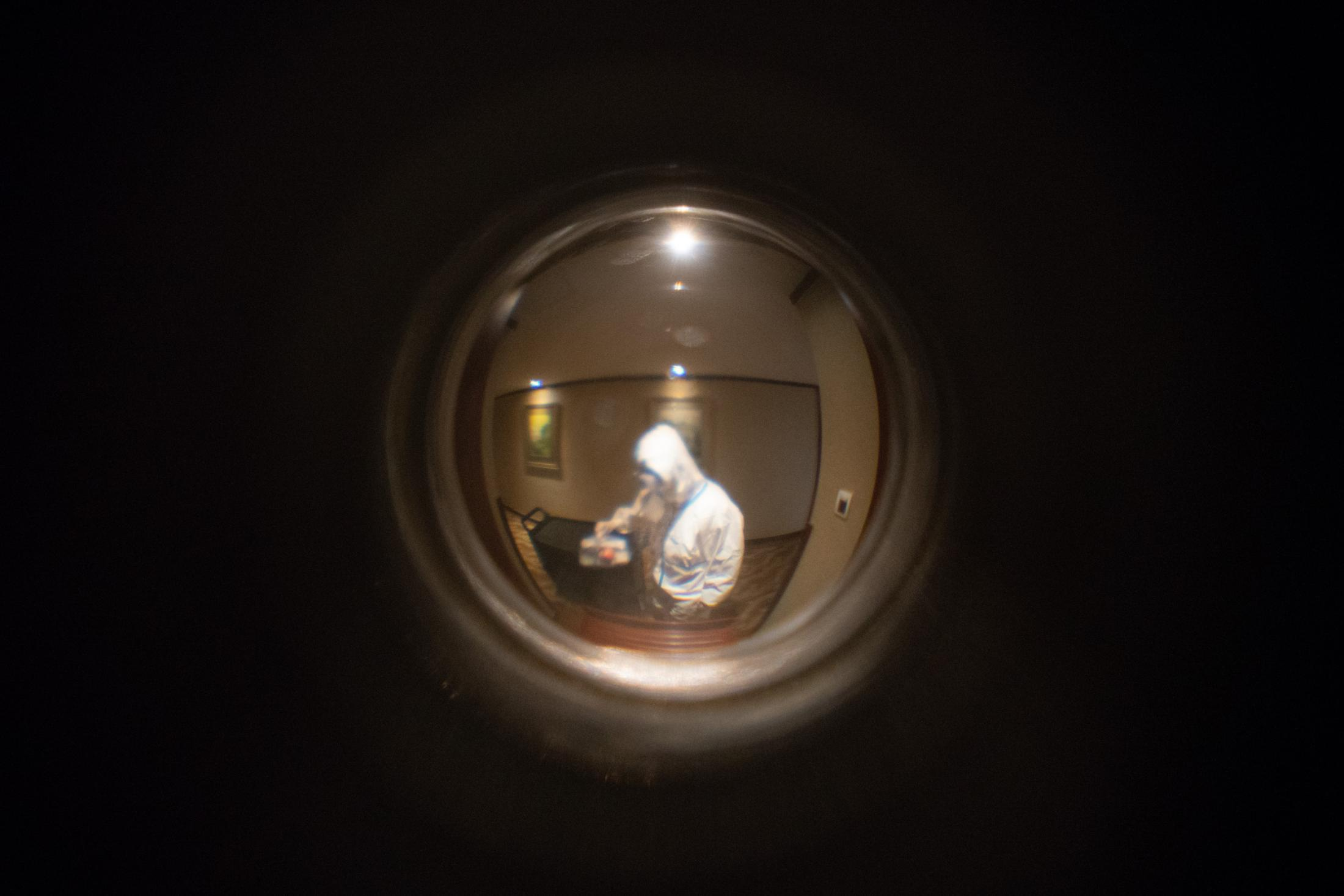 Seen through the peephole: a hotel staff taking a packed lunch from the cart to drop off outside my door.