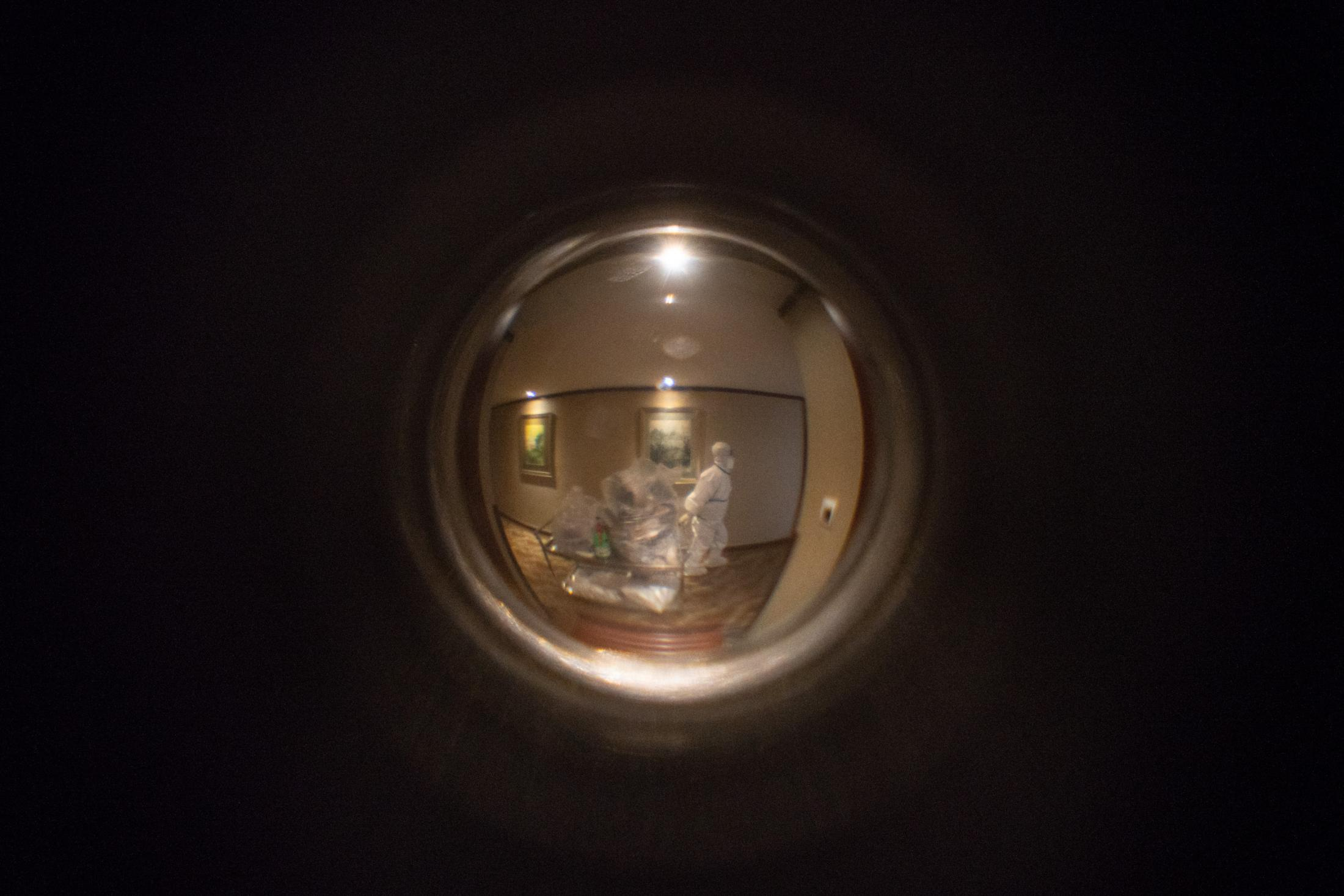 Seen through the peephole: a hotel staff dragging a cart full of trash taken from outside of each hotel rooms.