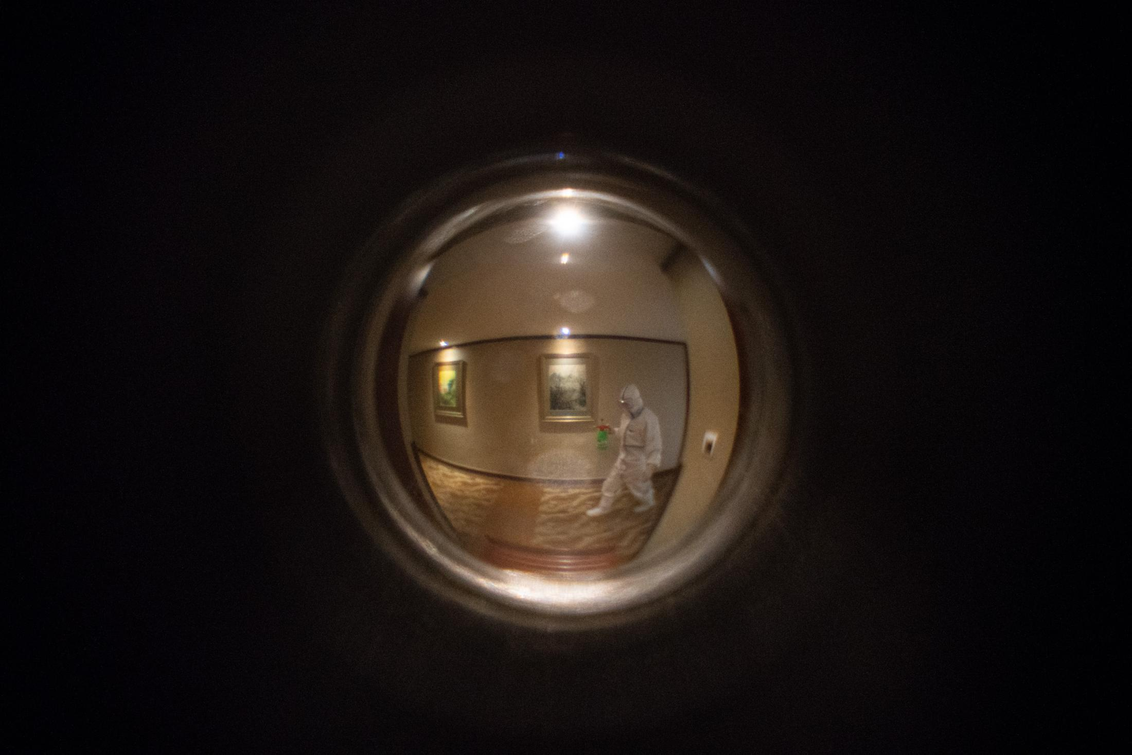 Seen through the peephole: a hotel staff walking with a spray bottle to disinfect the hallway.