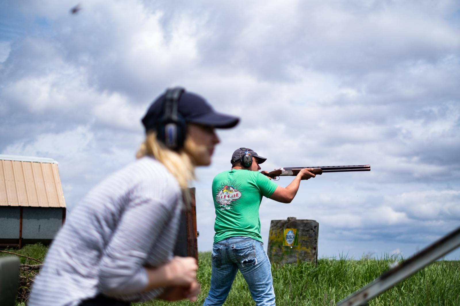 My brother fires at a clay pigeon that his girlfriend released from the thrower.