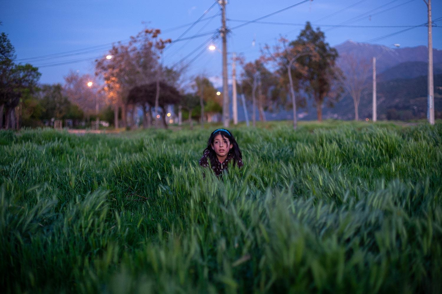 Yara playing in the grass near her home. Puente Alto, Chile. 2010