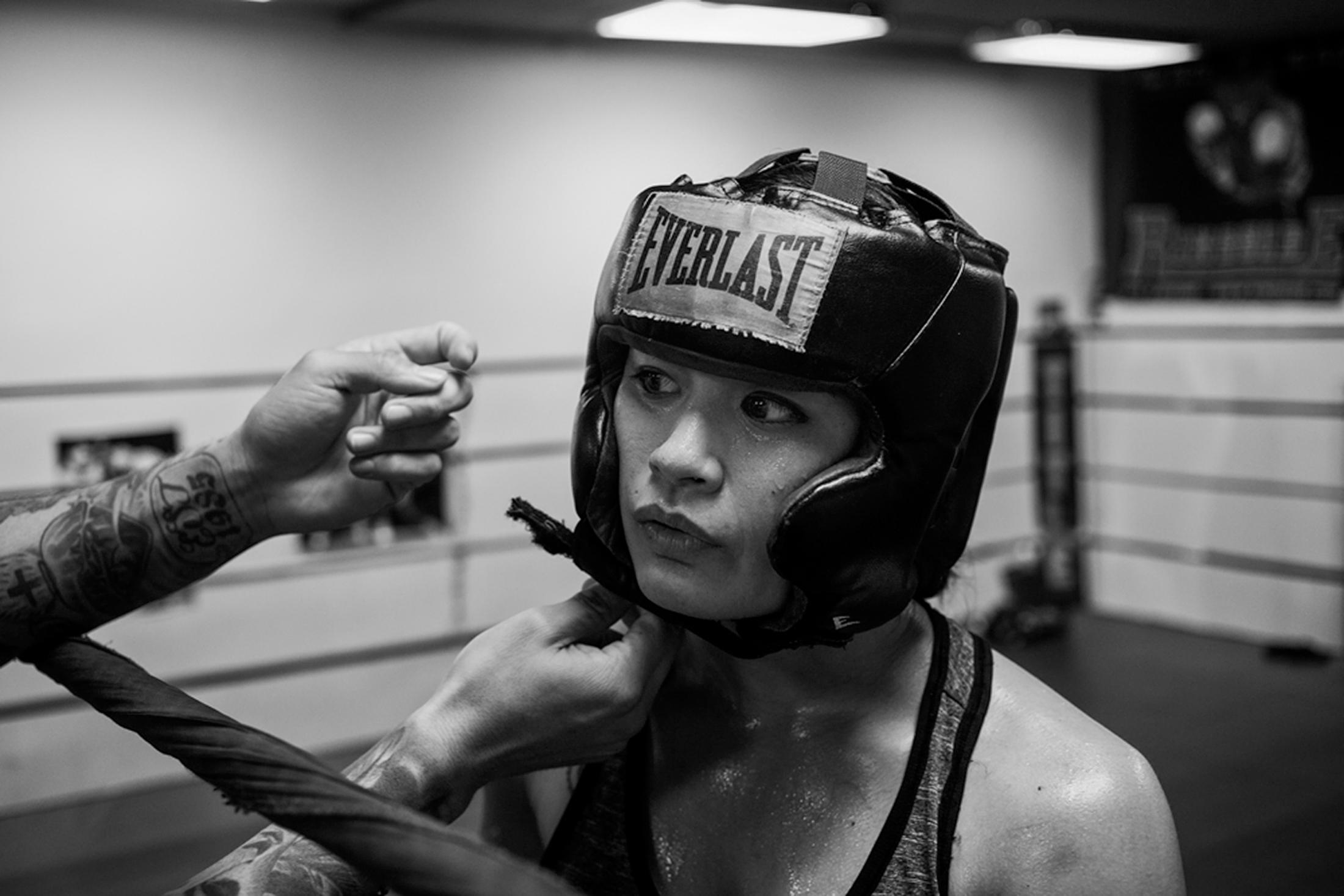 Casey is fitted with a helmet by her full-time coach, Jairo Escobar, before sparring with another female boxer at World Class Boxing Gym in San Francisco, CA.