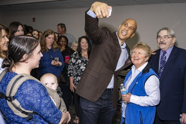 Cory Booker takes a selfie with Sue and Tom O'Dorisio of North Liberty while Theresa Lucin of Coralville watches with her six-month-old son Philip after giving a speech at the North Liberty Community Center in North Liberty on Monday, October 8, 2018. KC McGinnis for The Gazette